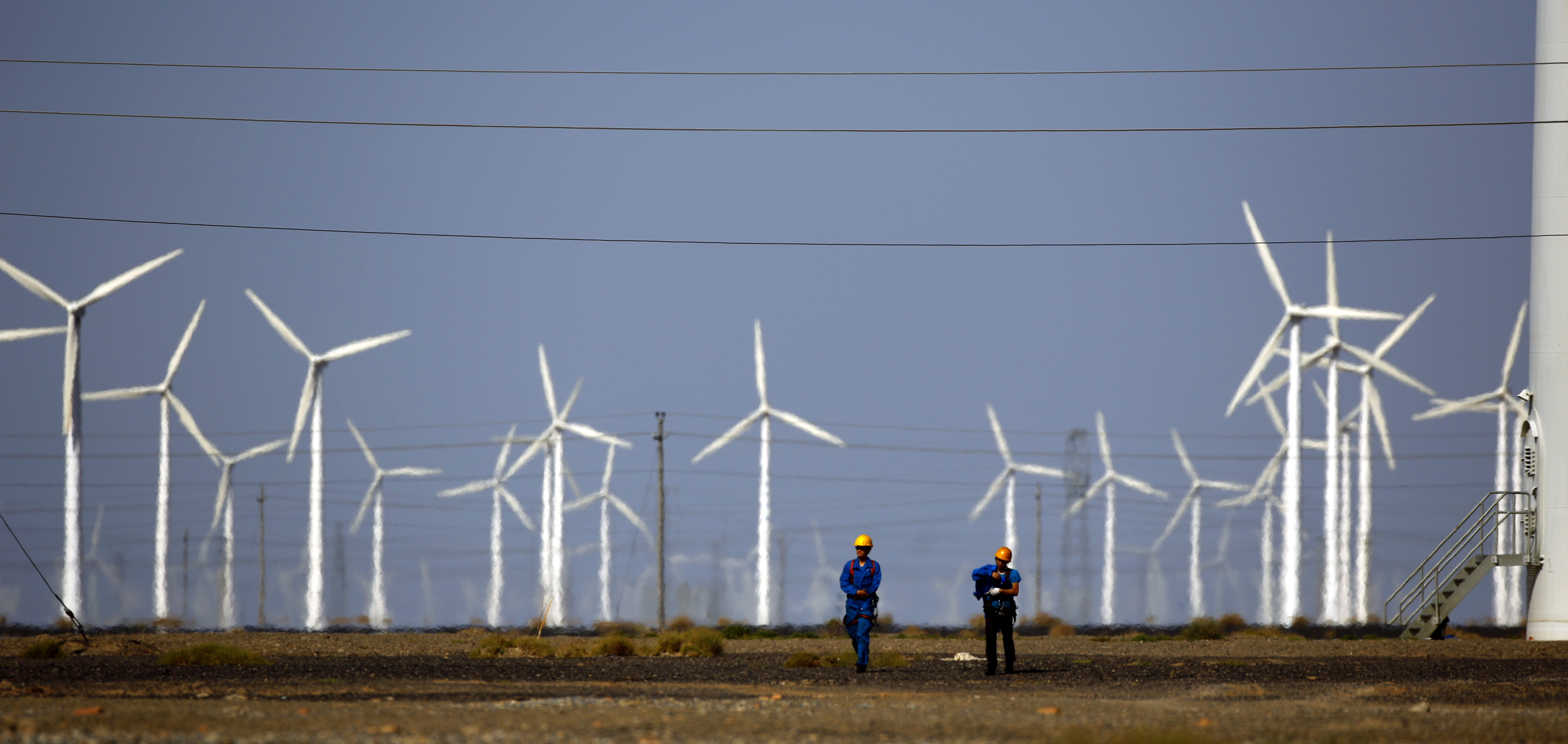 Workers walk near wind turbines for generating electricity, at a wind farm in Guazhou, 950km northwest of Lanzhou, Gansu Province