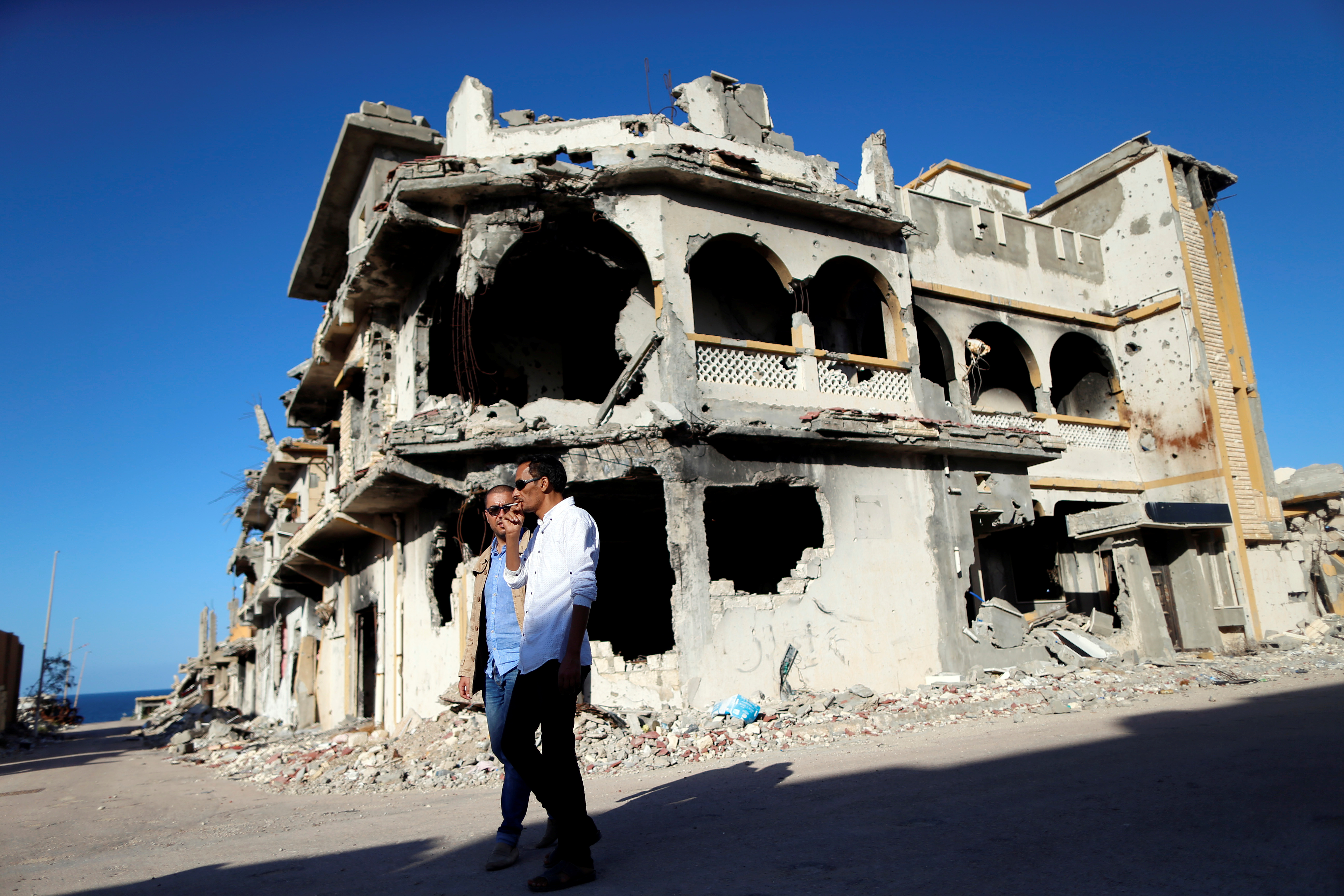 Men walk past the ruins of a building that was destroyed during clashes between Libyan forces and Islamic State militants, in Sirte, Libya, November 1, 2017. Picture taken November 1, 2017. REUTERS/Ahmed Jadallah - RC16BEF8E700