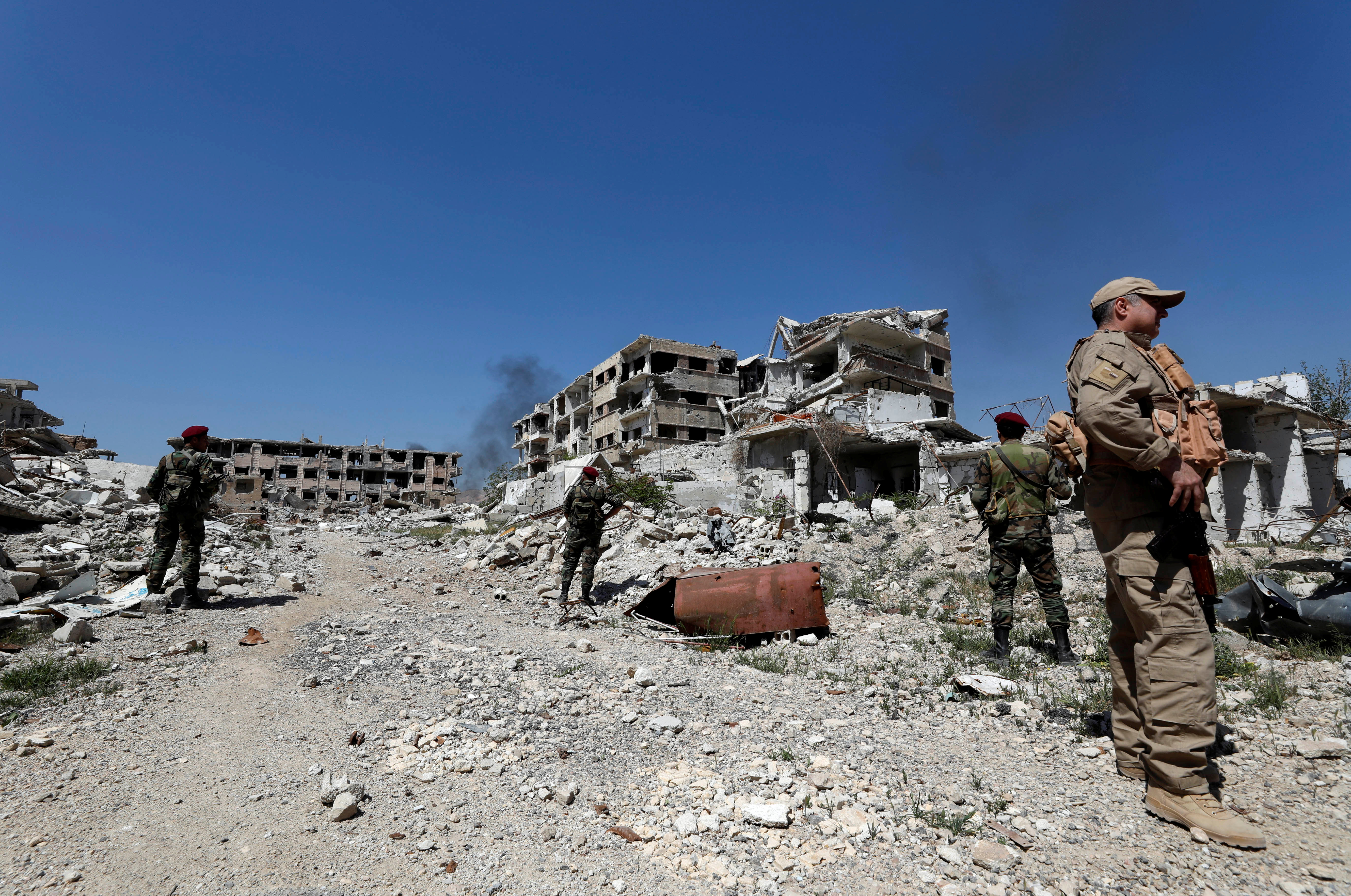 Members of Syrian forces of President Bashar al Assad stand guard near destroyed buildings in Jobar, eastern Ghouta, in Damascus, Syria April 2, 2018. REUTERS/Omar Sanadiki - RC1C4E863200