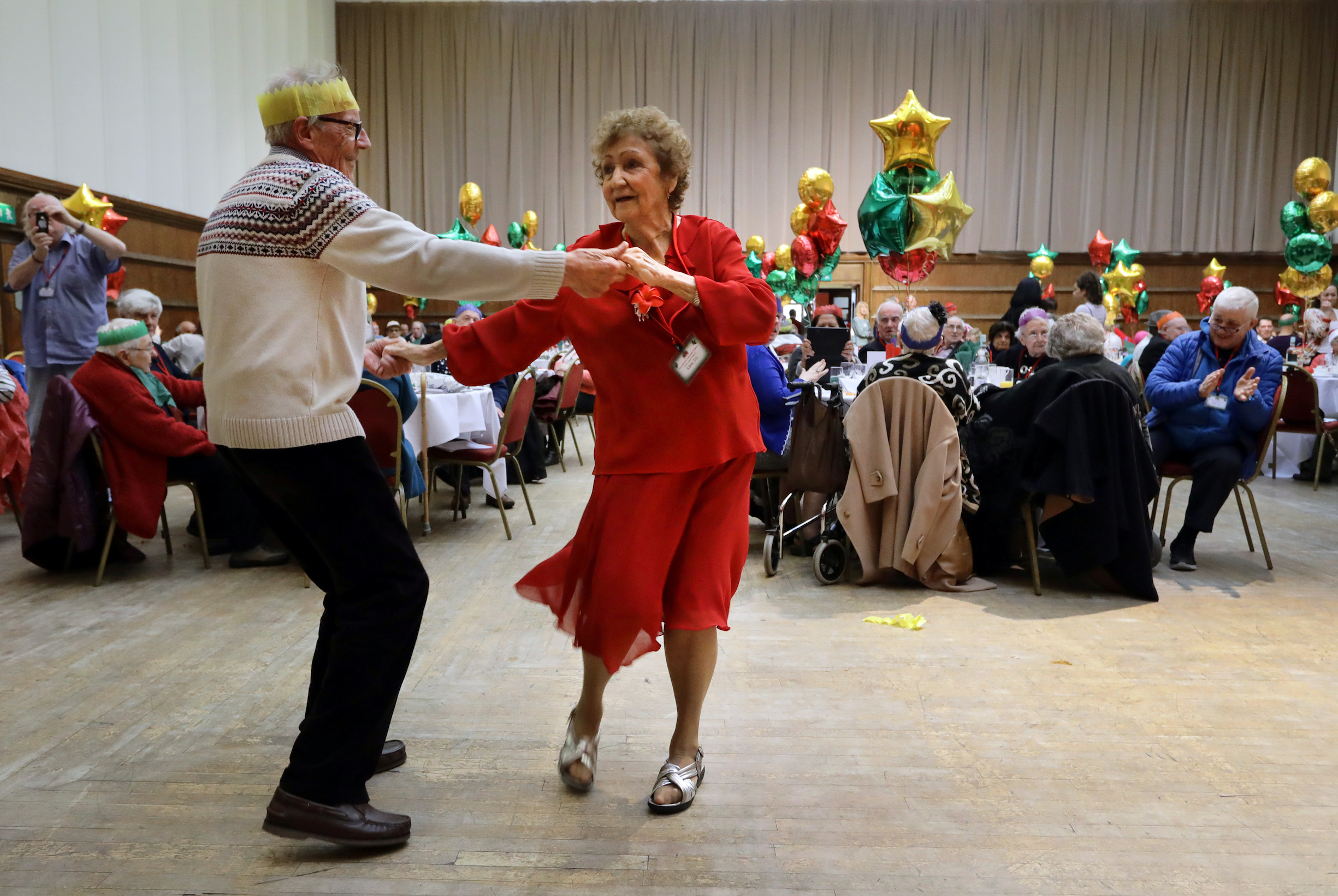 Anita Monk and her neighbour John Everett dance during a Christmas Dinner event for older people at Hammersmith and Fulham Town Hall in London, Britain December 25, 2016. REUTERS/Kevin Coombs - RC18585124A0