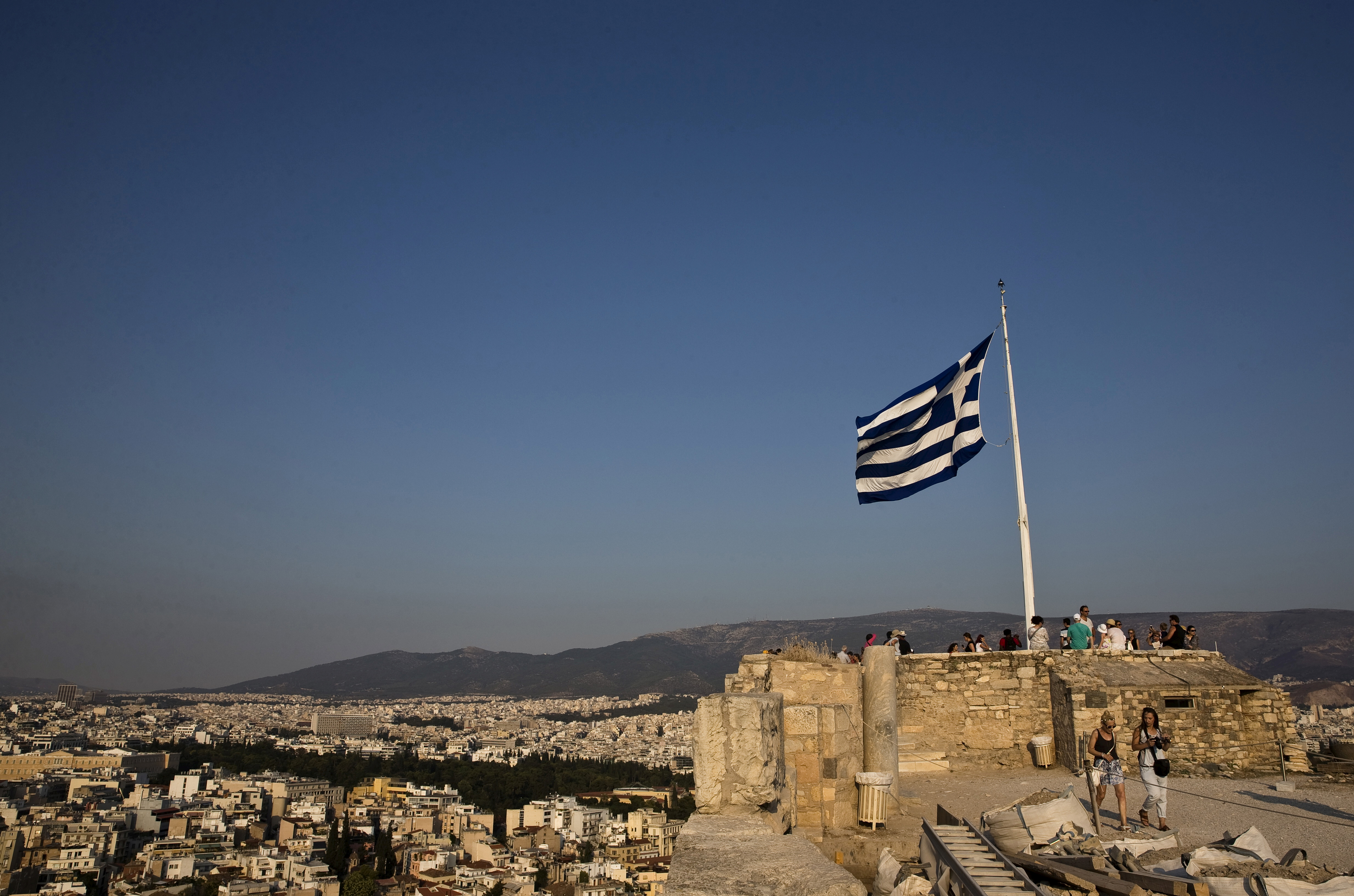 """A Greek flag flutters in the wind as tourists visit the archaeological site of the Acropolis hill in Athens, Greece July 26, 2015.   REUTERS/Ronen Zvulun/File Photo                      GLOBAL BUSINESS WEEK AHEAD - SEARCH """"GLOBAL BUSINESS AUG 29"""" FOR ALL IMAGES? - S1AETYDHNXAA"""