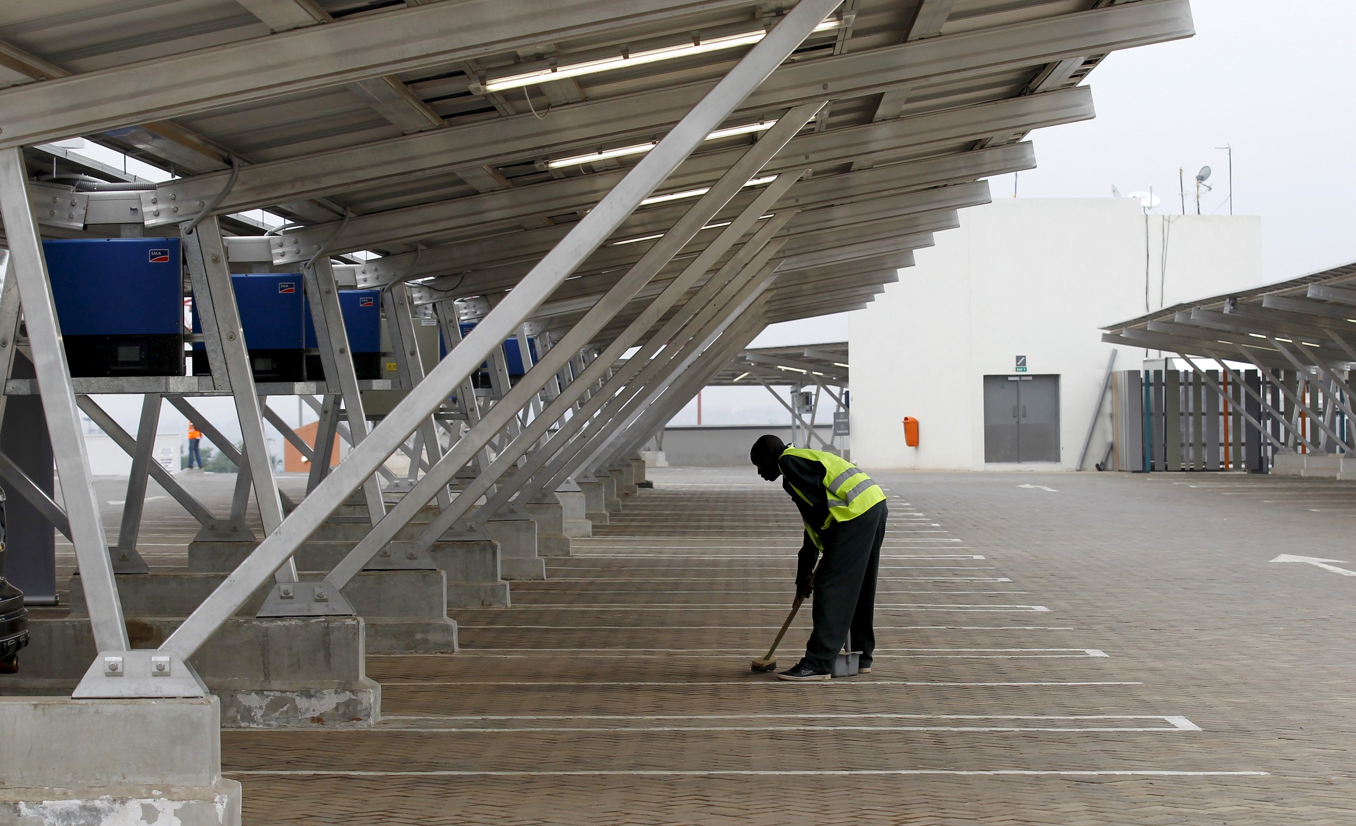A worker sweeps the floor under solar panels which provide shade for vehicles at a solar carport at the Garden City shopping mall in Kenya's capital Nairobi, September 15, 2015. The Africa's largest solar carport with 3,300 solar panels will generate 1256 MWh annually and cut carbon emission by around 745 tonnes per year, according to Solarcentury and Solar Africa.  REUTERS/Thomas Mukoya - GF10000206552