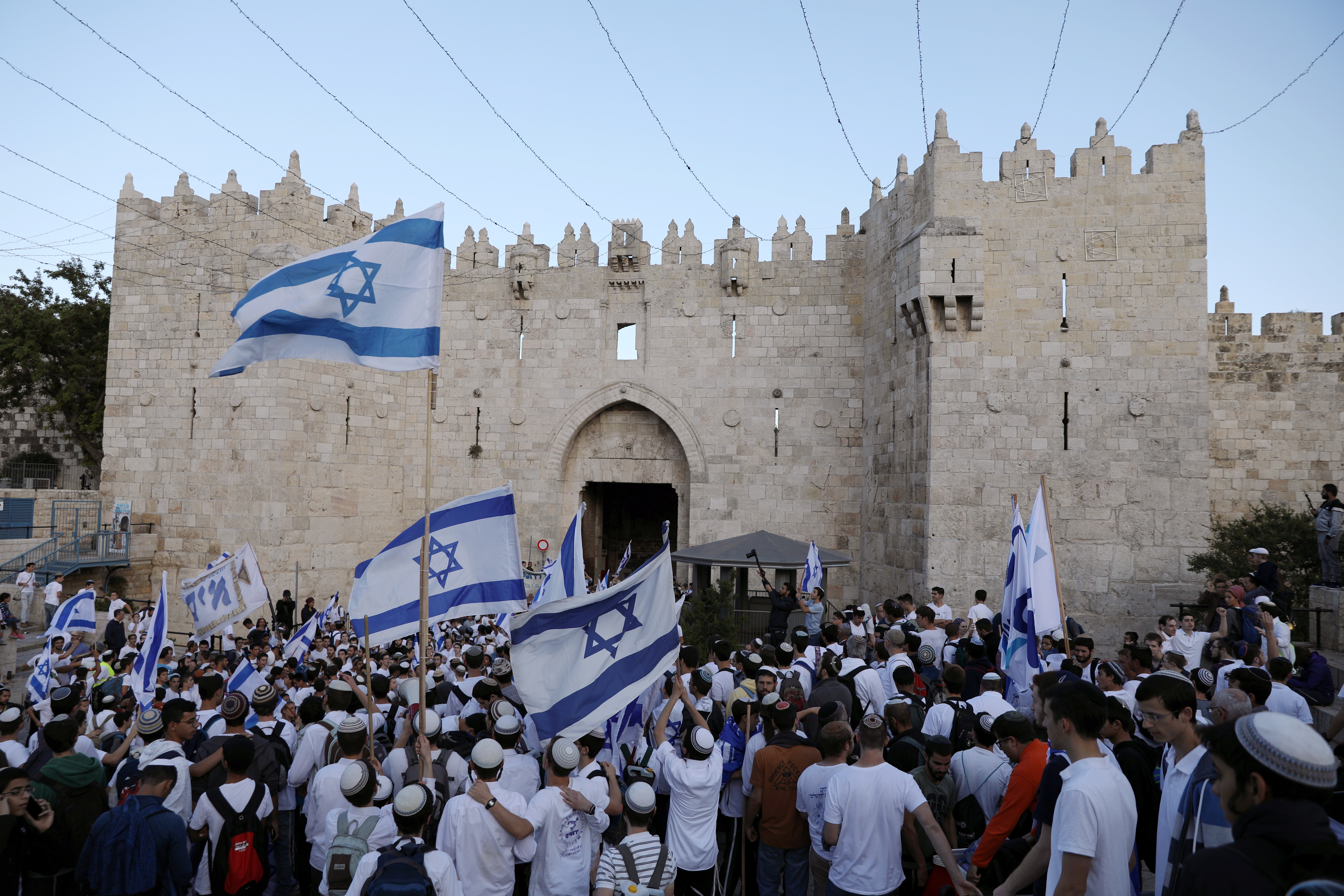 Israelis celebrate as they hold Israeli flags during a parade marking the annual Jerusalem Day, at Damascus Gate in Jerusalem's Old City, May 13, 2018. REUTERS/Ammar Awad - RC1A6A0D5F10