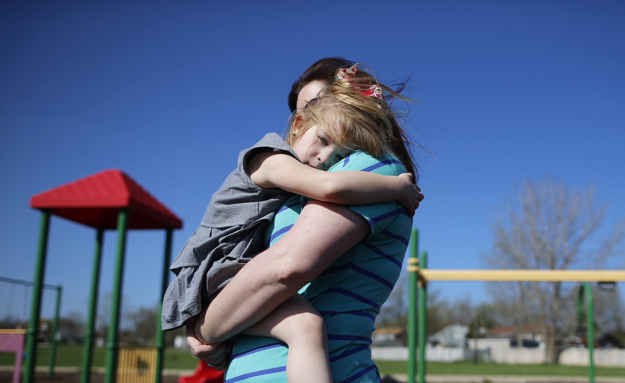 A young woman holds her daughter at a playground in Winthrop Harbor, Illinois.