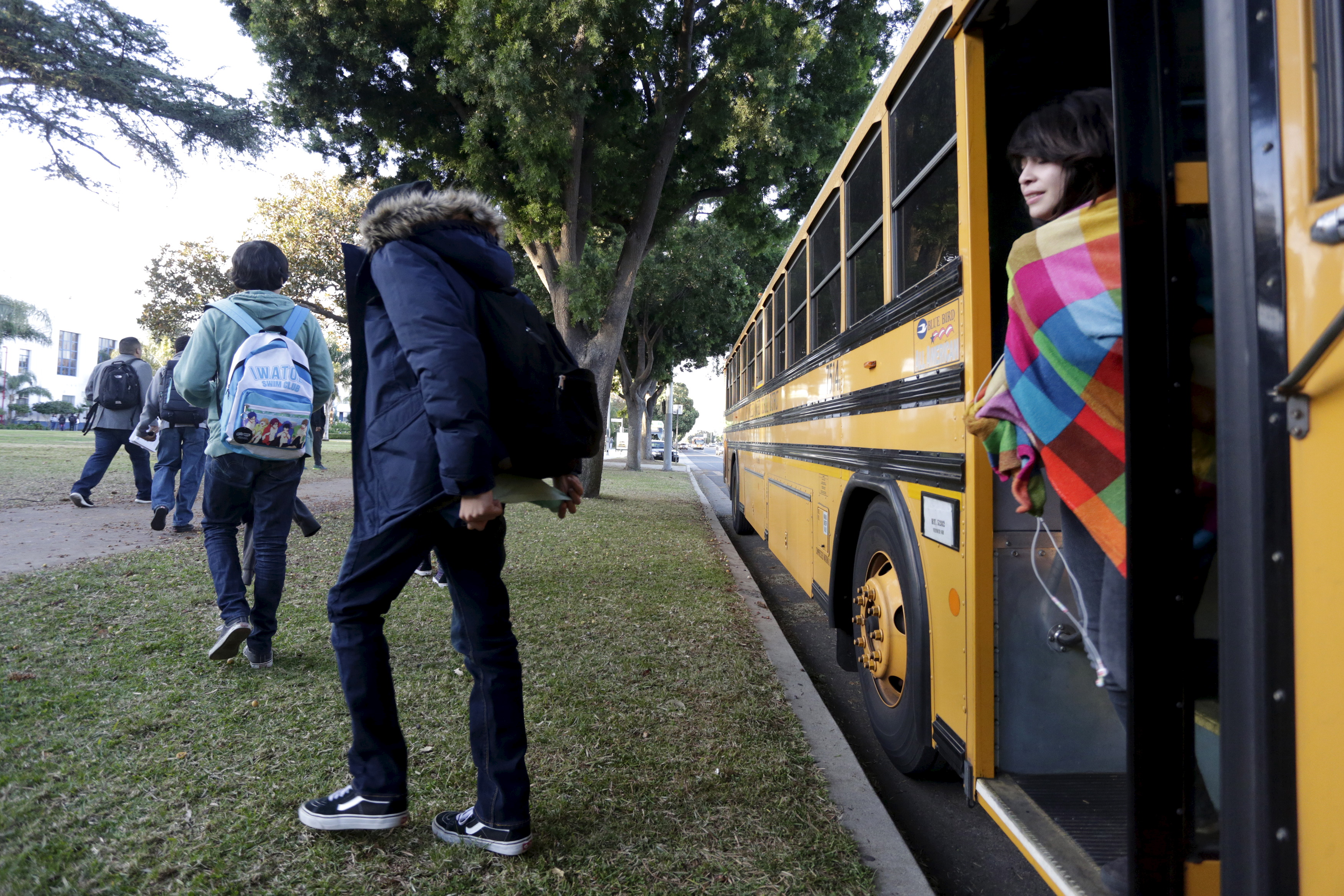 Students exit a bus as they arrive at Venice High School in Los Angeles.