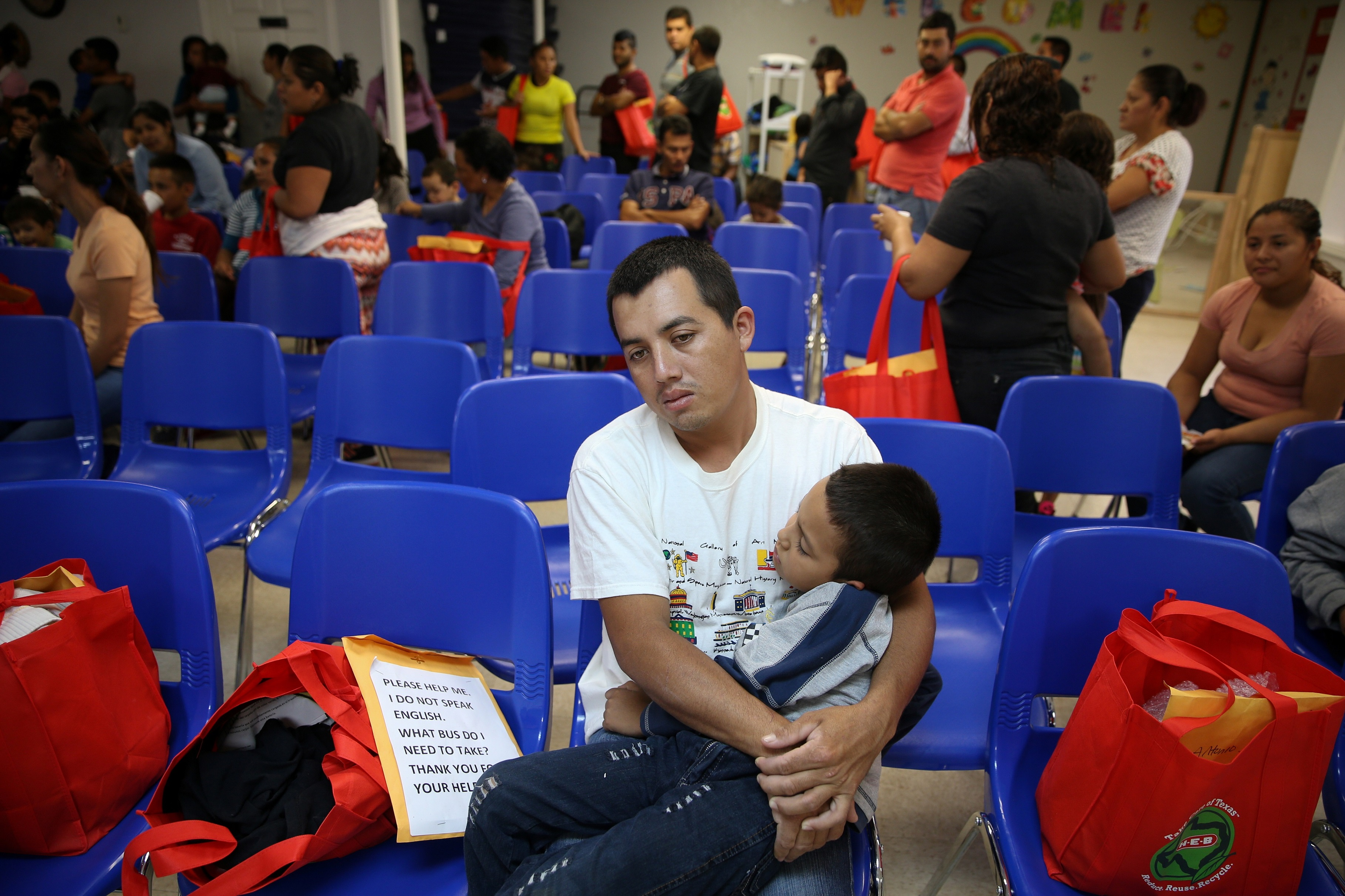"""An undocumented immigrant from Honduras and his son, recently released from detention through """"catch and release"""" immigration policy, pass the time before beginning a bus journey to Louisiana at the Catholic Charities relief center in McAllen, Texas, U.S., April 6, 2018.  REUTERS/Loren Elliott - RC1B544F5750"""