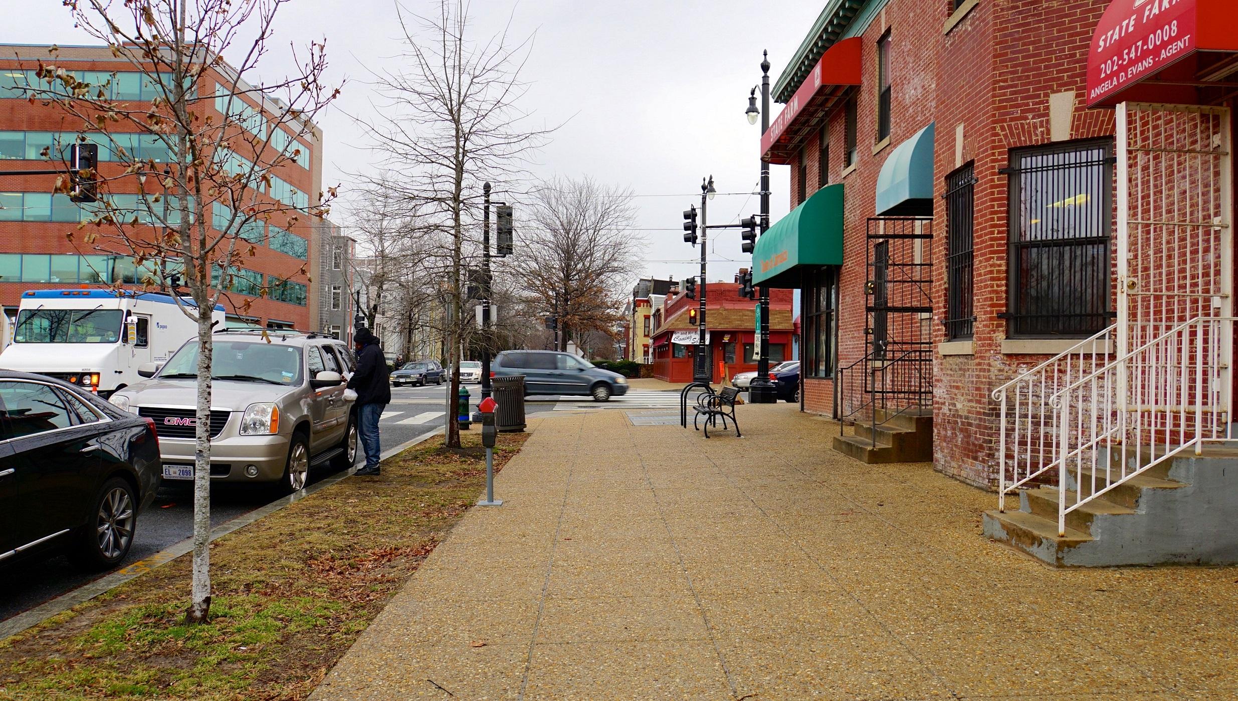 Pedestrian pass shuttered buildings in Ward 8 in Washington DC.