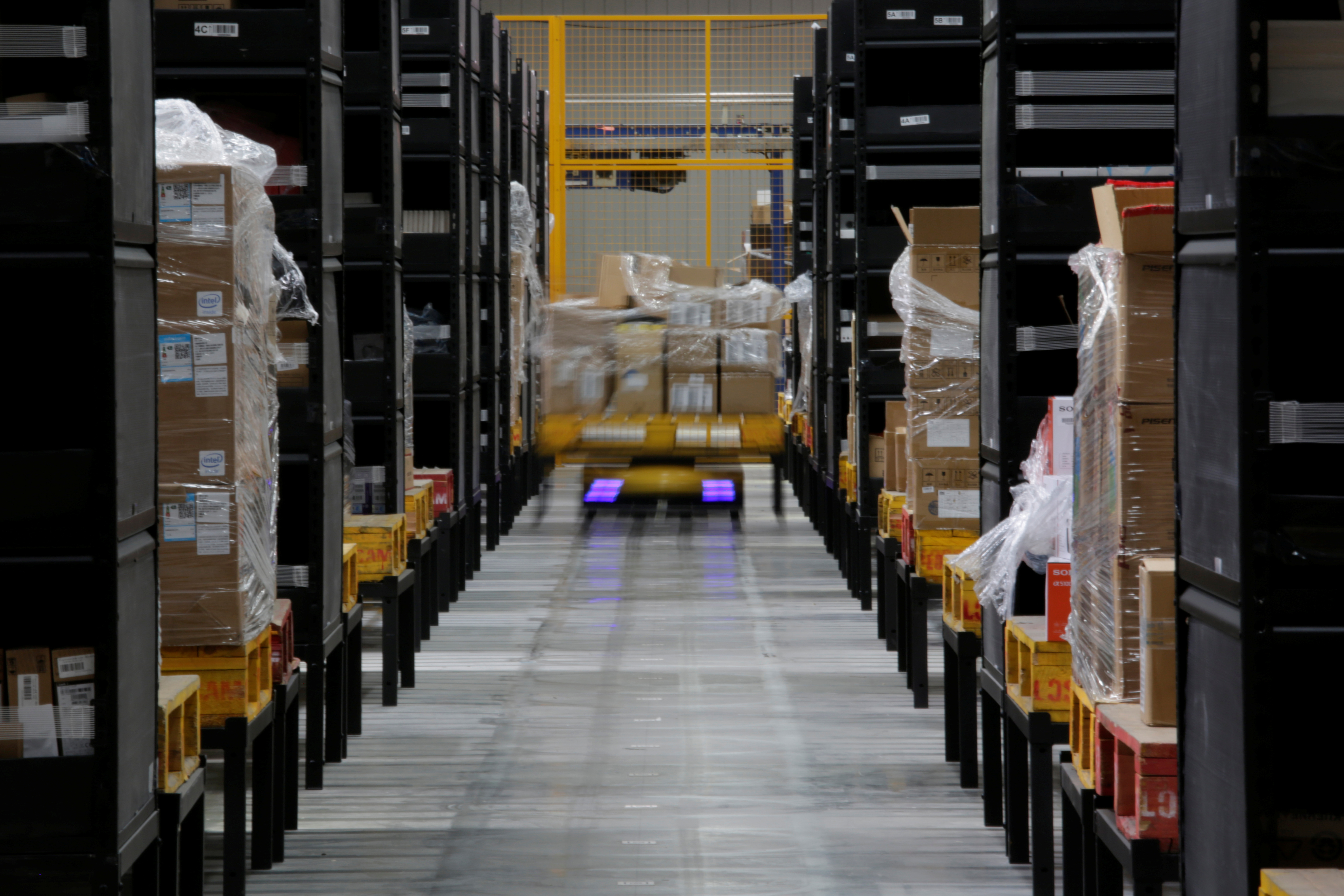 A robot moves goods through stocking shelves