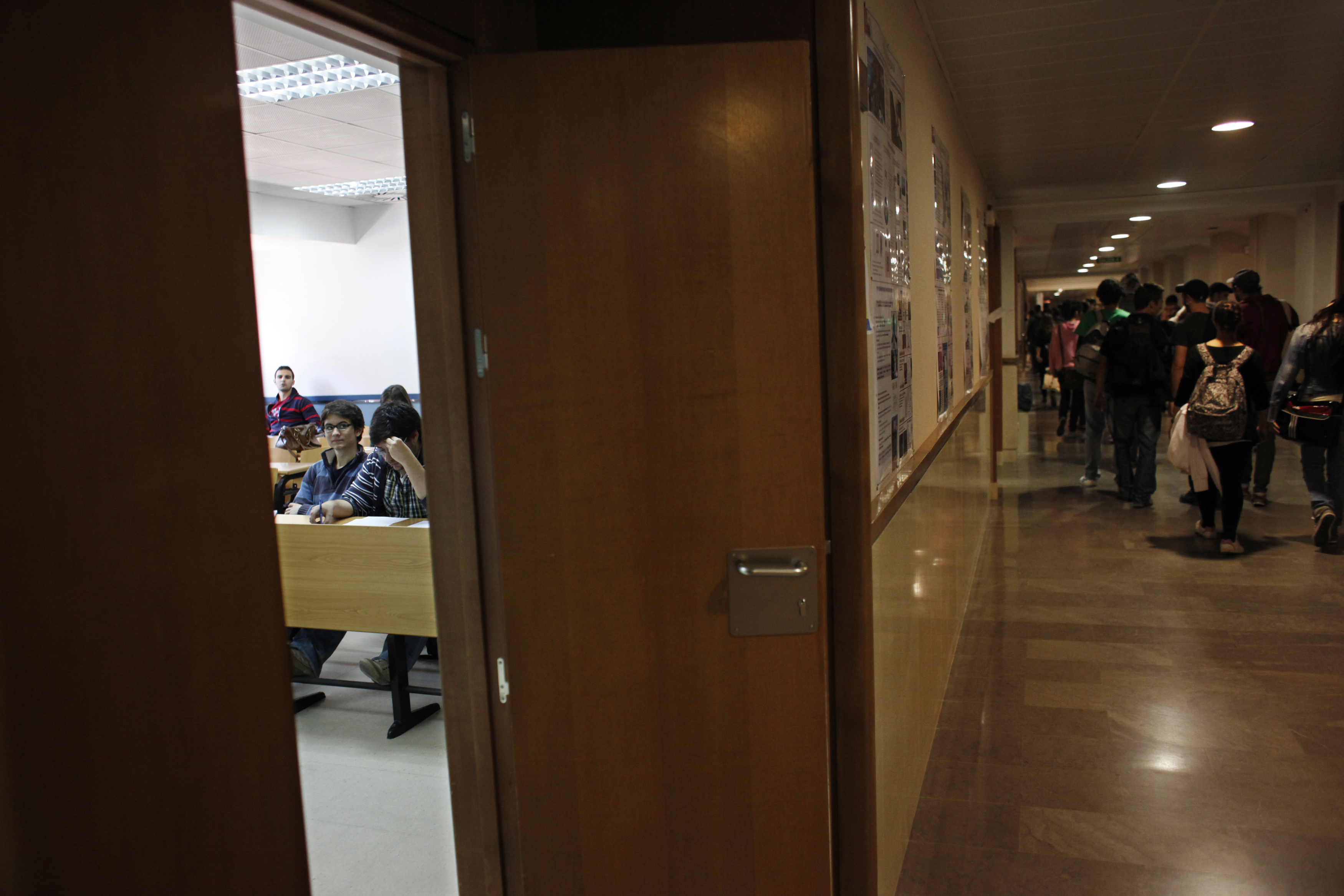 A handful of students attend class as other student picketers walk the hallways at Madrid's Complutense University during a general teachers' strike against educational cuts imposed by the Spanish government May 22, 2012. Spanish teachers went on strike on Tuesday to protest against cuts in education spending that labour unions say will put 100,000 substitute teachers out of work but that the government says are needed to tackle the euro zone debt crisis. REUTERS/Susana Vera (SPAIN - Tags: EDUCATION CIVIL UNREST) - GM1E85M1LOP01