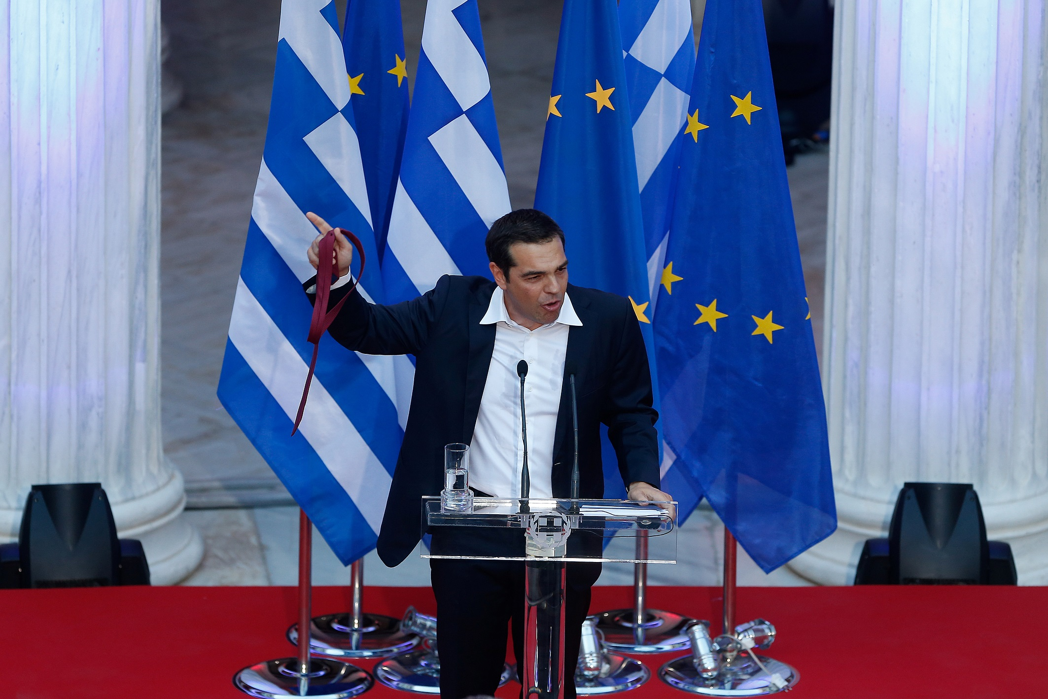 Greek Prime Minister Alexis Tsipras holds his tie as he speaks at the parliamentary group of Syriza and Independent Greeks in Athens, Greece, June 22, 2018.REUTERS/Costas Baltas - RC1866D1E820