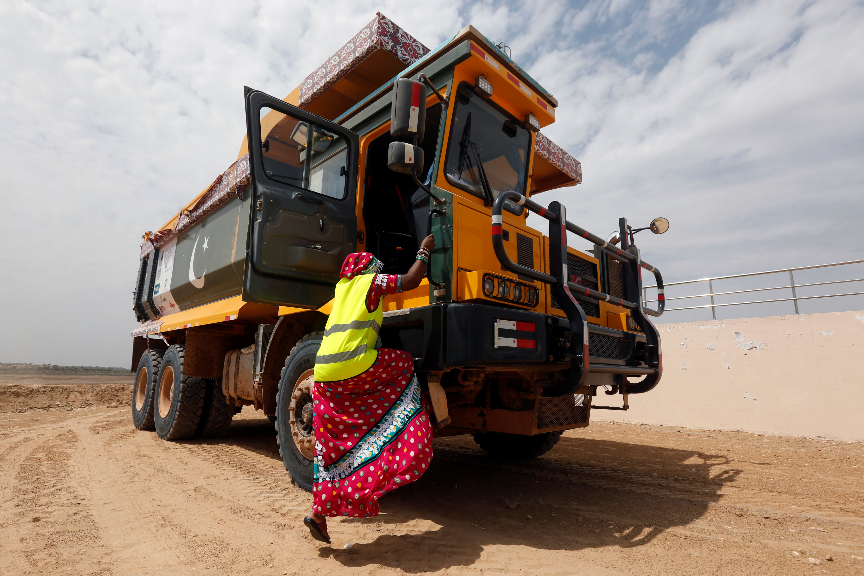 Gulaban, 25, mother of three, climbs into a 60-tonne truck, during a training session of the Female Dump Truck Driver Programme, held by the Sindh Engro Coal Mining Company (SECMC), in Islamkot, Tharparkar, Pakistan September 21, 2017. Picture taken September 21, 2017. REUTERS/Akhtar Soomro - RC14E23BF690