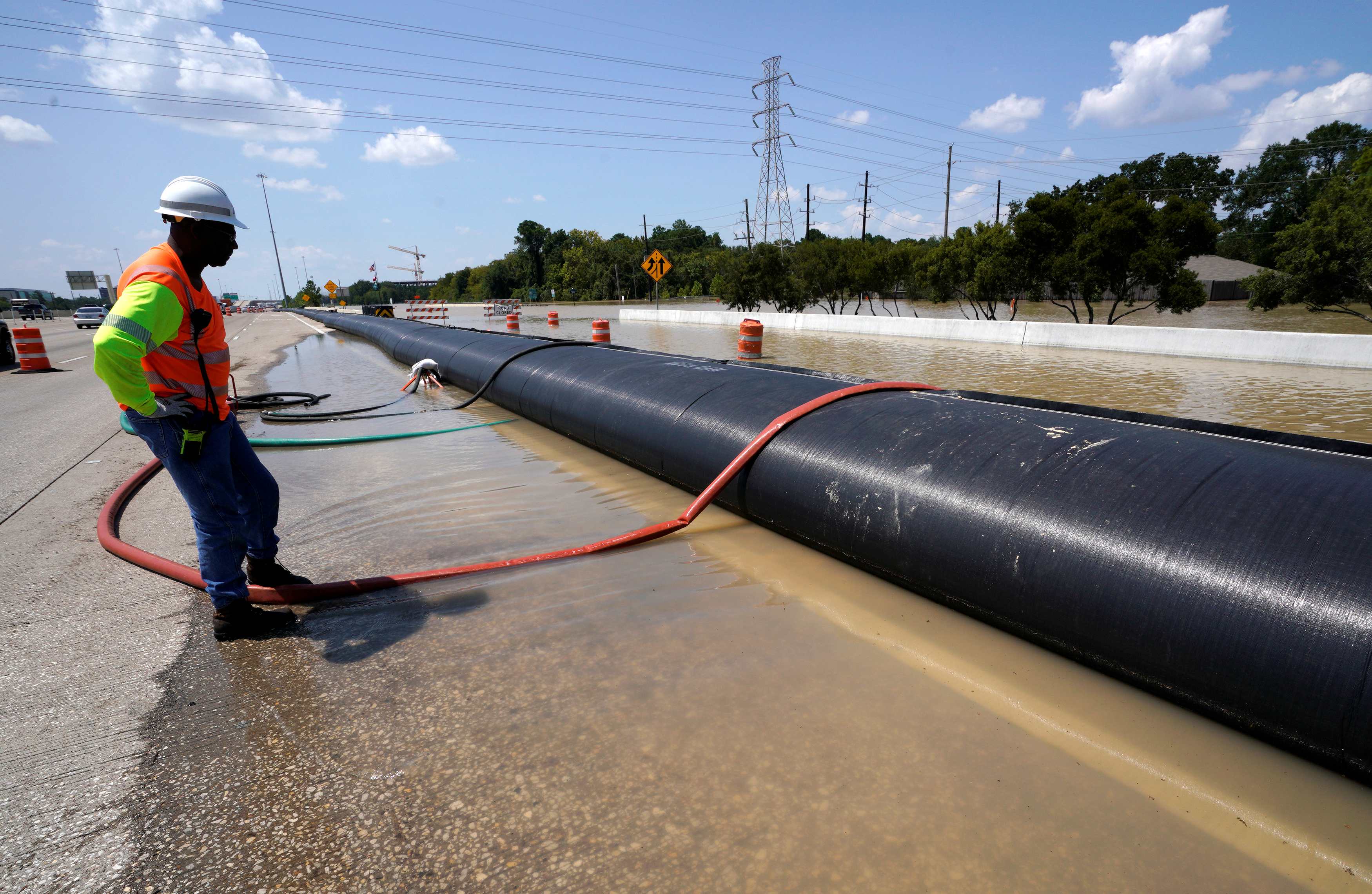 A Texas Department of Transportation worker monitors a temporary water filled dam keeping Harvey floodwaters from getting onto highway I-10 in Houston, Texas August 31, 2017. REUTERS/Rick Wilking - RC1FDAADF450