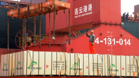 A worker gestures as a crane lifts goods onto a cargo ship, at a port in Lianyungang, Jiangsu province, China May 31, 2018. Picture taken May 31, 2018. REUTERS/Stringer   ATTENTION EDITORS - THIS IMAGE WAS PROVIDED BY A THIRD PARTY. CHINA OUT. - RC180A124BF0