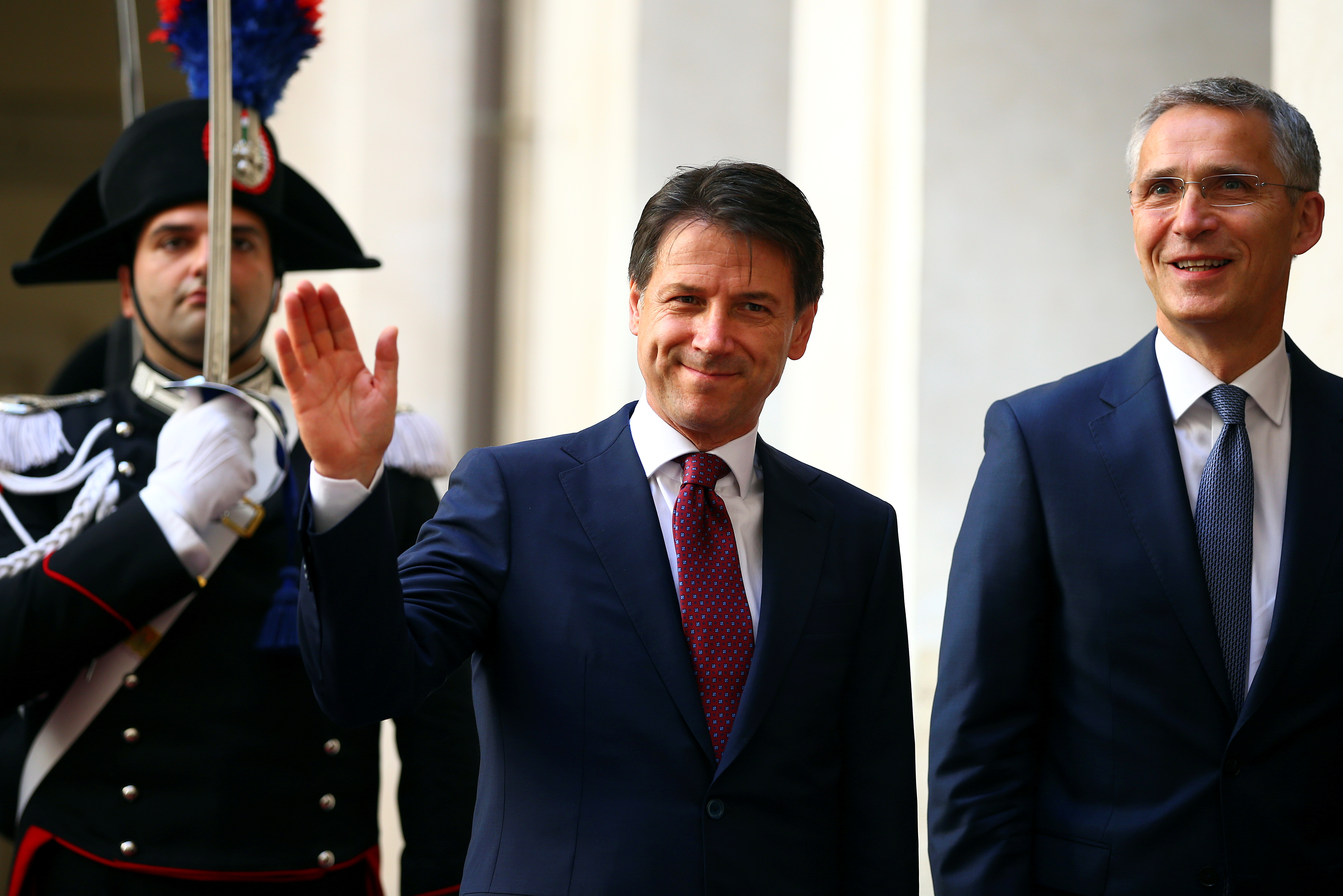 Italy's Prime Minister Giuseppe Conte waves as he arrives with NATO Secretary-General Jens Stoltenberg at Chigi palace in Rome, Italy, June 11, 2018.  REUTERS/Tony Gentile - RC1AFEEA6610
