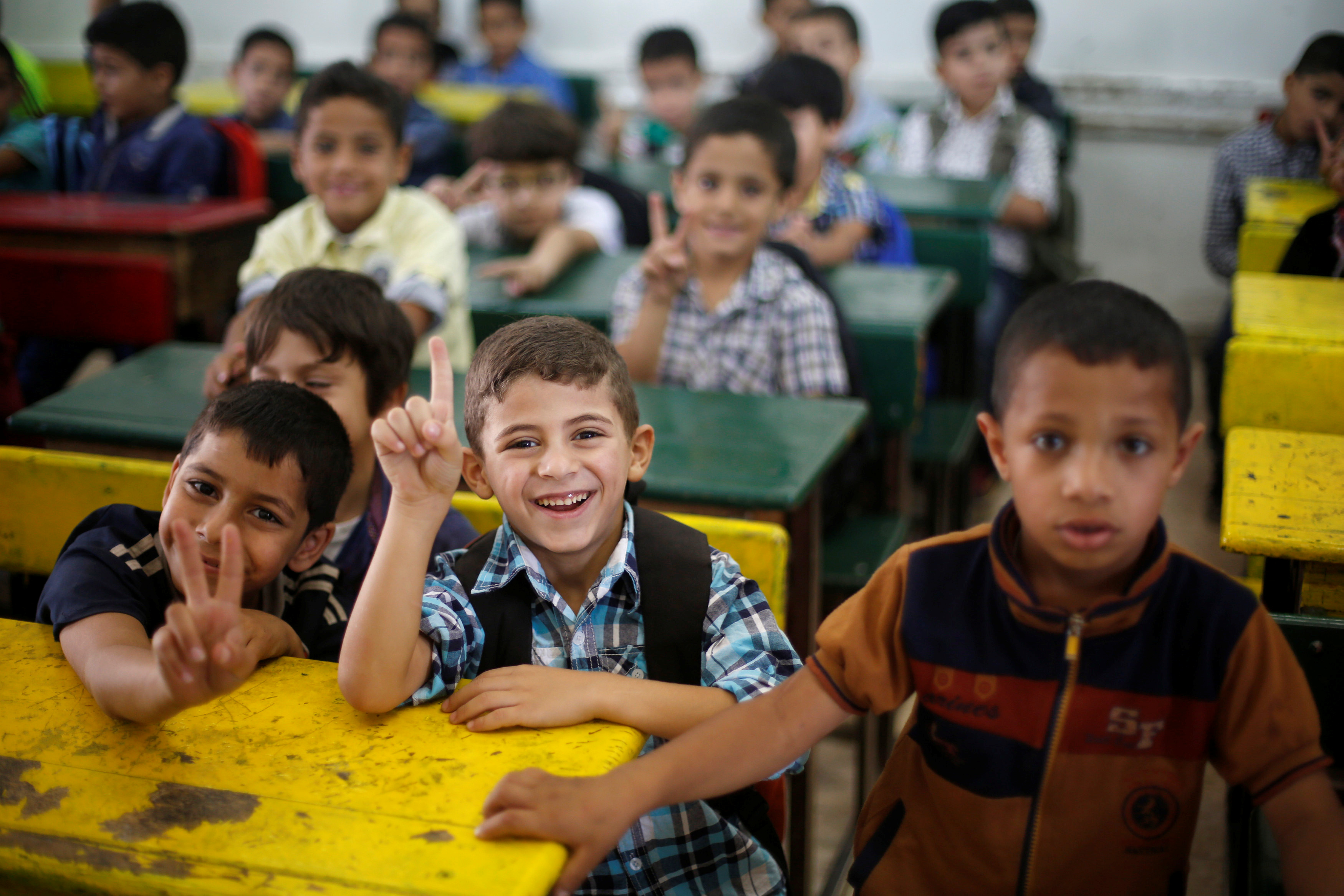 Schoolchildren react to the camera as they attend a lesson in a classroom on the first day of school
