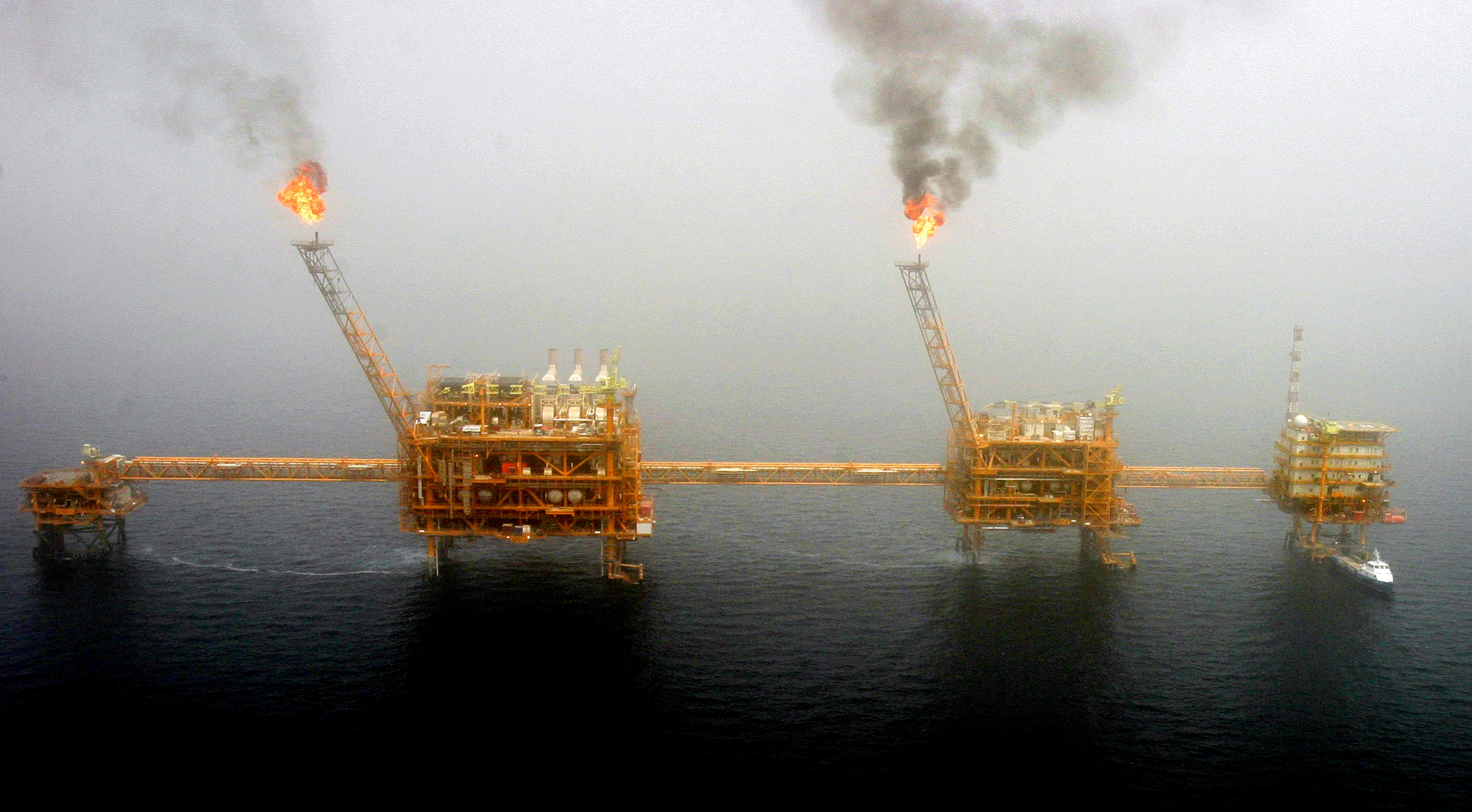 Gas flares from an oil production platform at the Soroush oil fields in the Persian Gulf, south of the capital Tehran, July 25, 2005.  REUTERS/Raheb Homavandi/File Photo - S1AETIFZOIAA