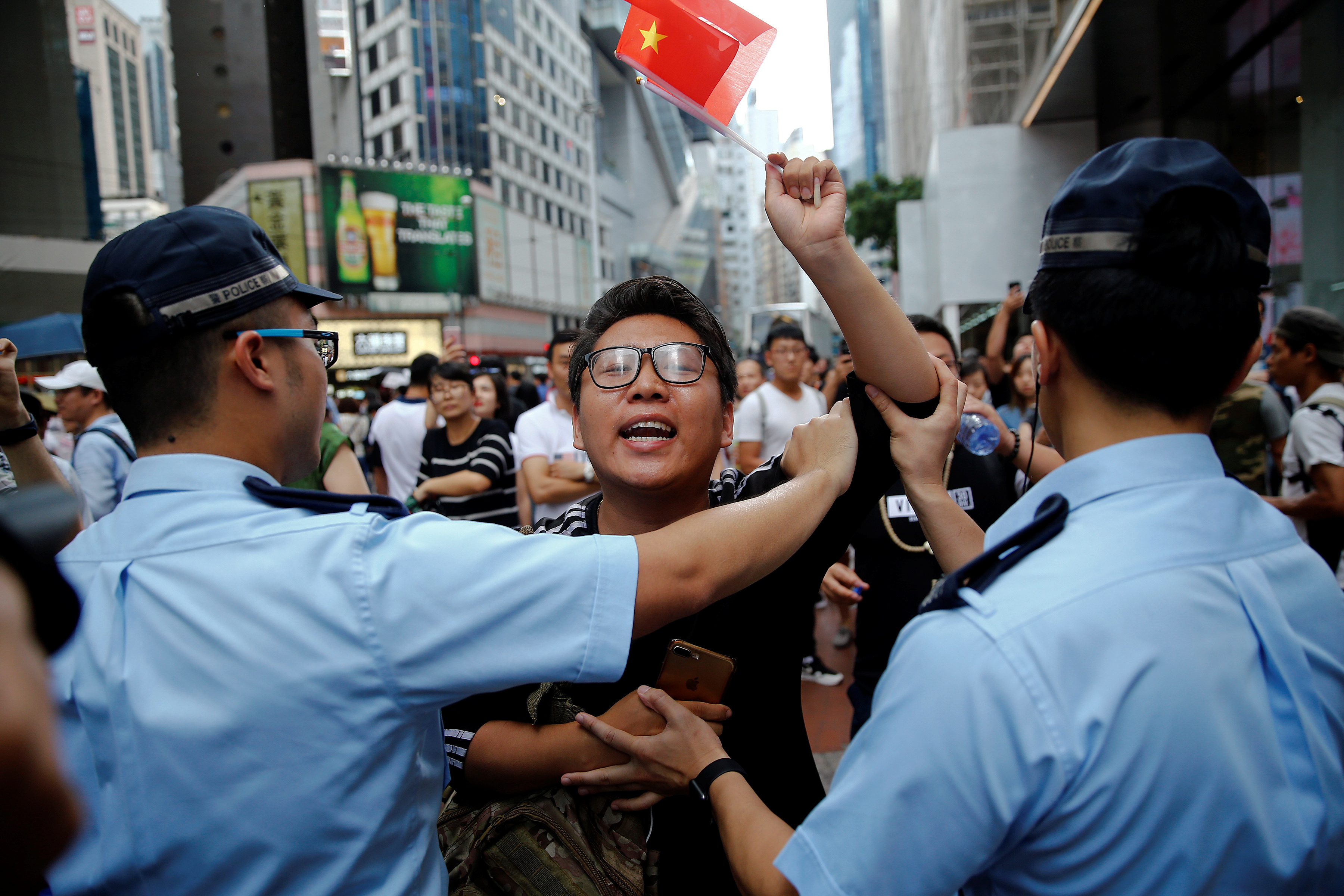 A pro-China supporter is stopped by police as he tries to get closer to pro-democracy supporters during a march. Hong Kong, China July 1, 2017. REUTERS/Damir Sagolj