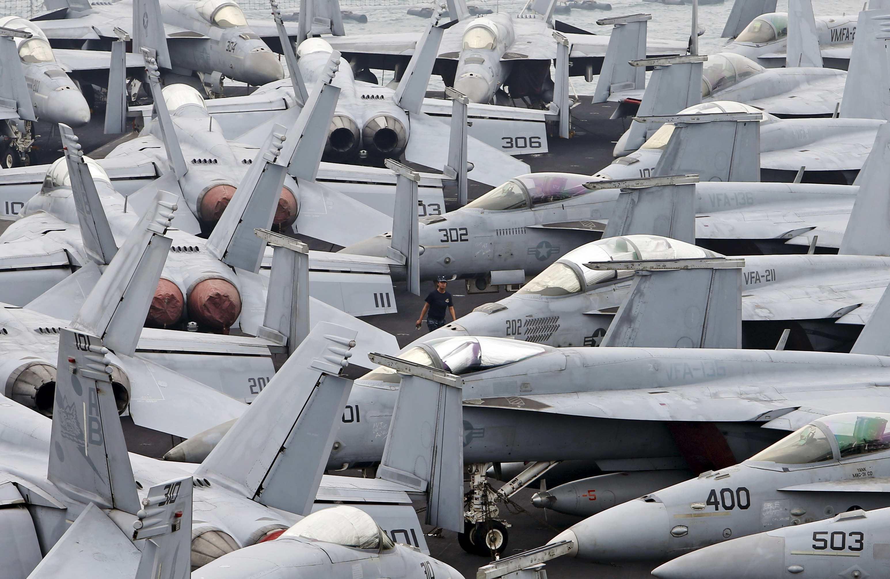 A U.S. Navy personnel walks among F/A 18 aircraft on the flight deck of the USS Theodore Roosevelt at Changi Navy Base in Singapore October 24, 2015. The aircraft carrier and its strike group of 7 ships and 80 aircraft docked in Singapore on Saturday after completing a deployment to the Arabian Gulf for the last 7 months. REUTERS/Edgar Su  - GF20000030490