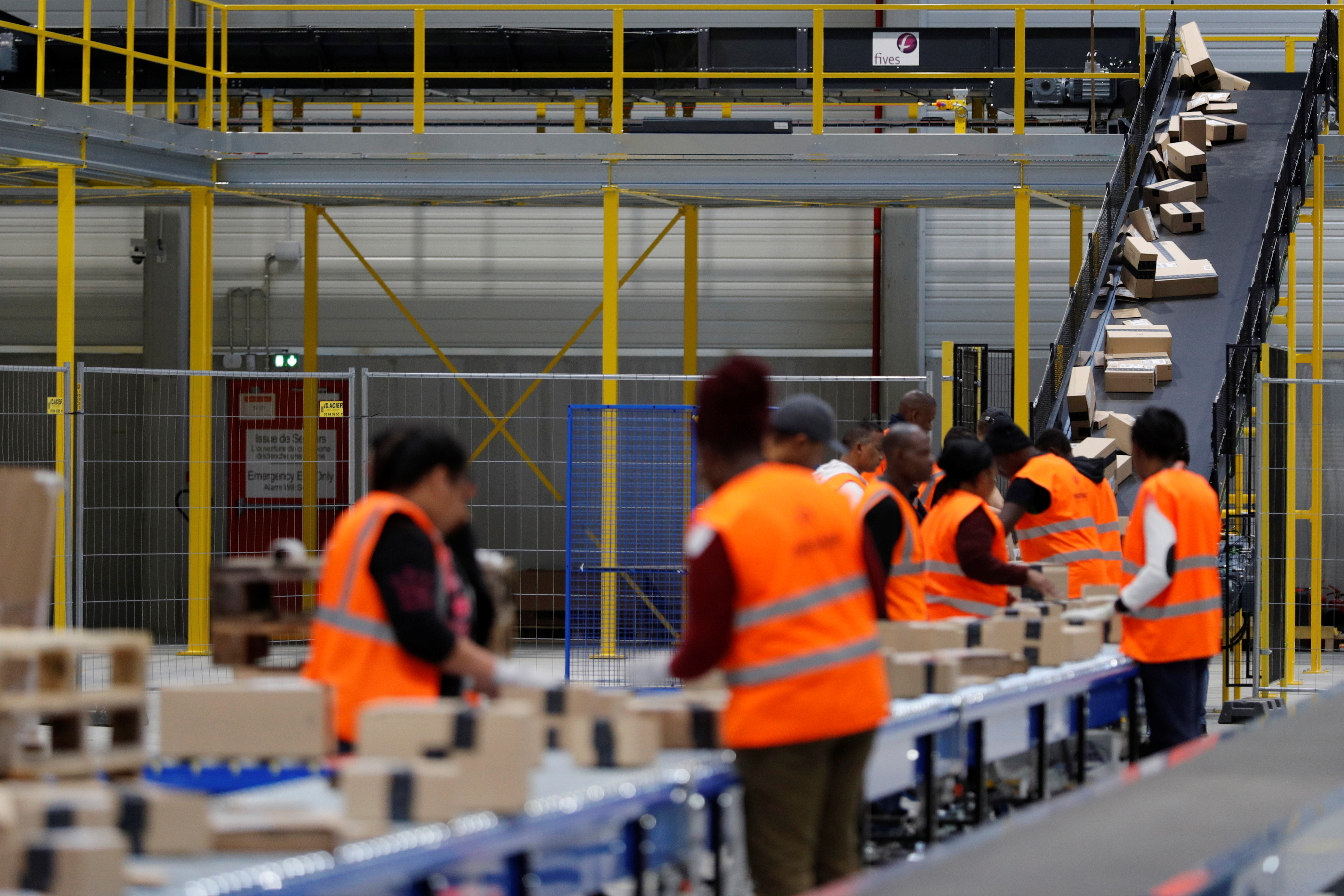 Employees sort packages at the Amazon distribution center warehouse in Saran, near Orleans, France, November 22, 2016.   REUTERS/Philippe Wojazer - RC184ABAB660