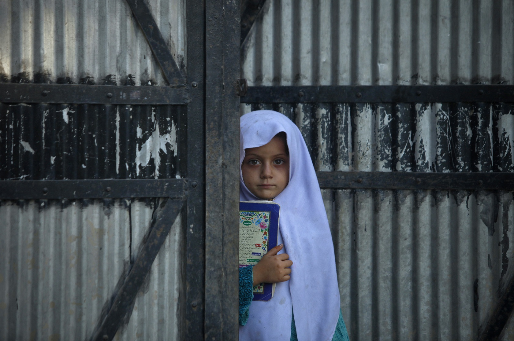 Noreen, a 6-year-old Pashtun girl, holds a book as she stands at the doorway of her family house in the outskirts of Peshawar October 11, 2012.  REUTERS/Fayaz Aziz     (PAKISTAN - Tags: SOCIETY TPX IMAGES OF THE DAY) - GM1E8AB1TKJ01