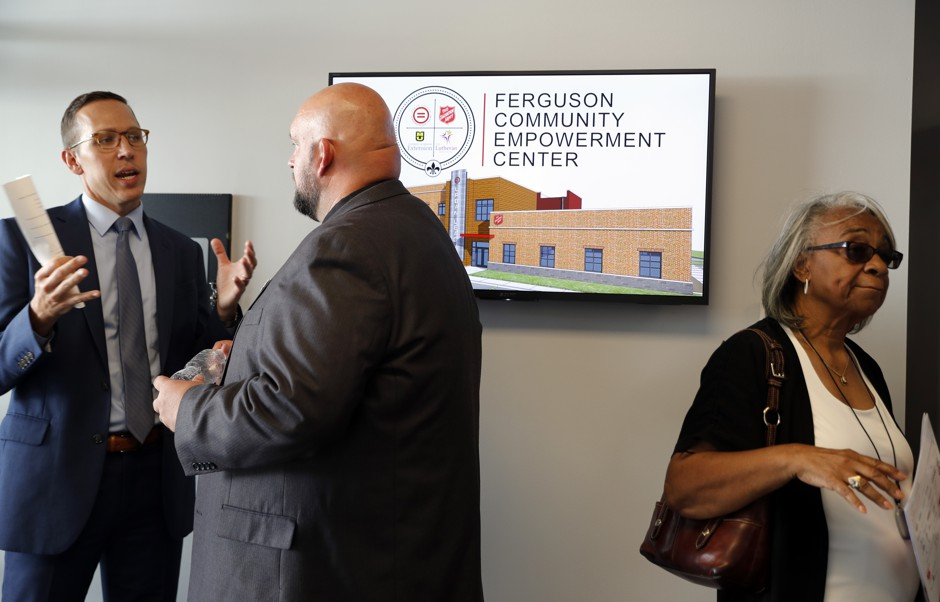 People gather in the lobby of a new community empowerment center during a following a dedication ceremony for the building Wednesday, July 26, 2017, in Ferguson, Mo. The $3-million Ferguson Community Empowerment Center was built on the property where a QuikTrip convenience store was burned during rioting after a white officer fatally shot Michael Brown nearly three years ago. (AP Photo/Jeff Roberson)