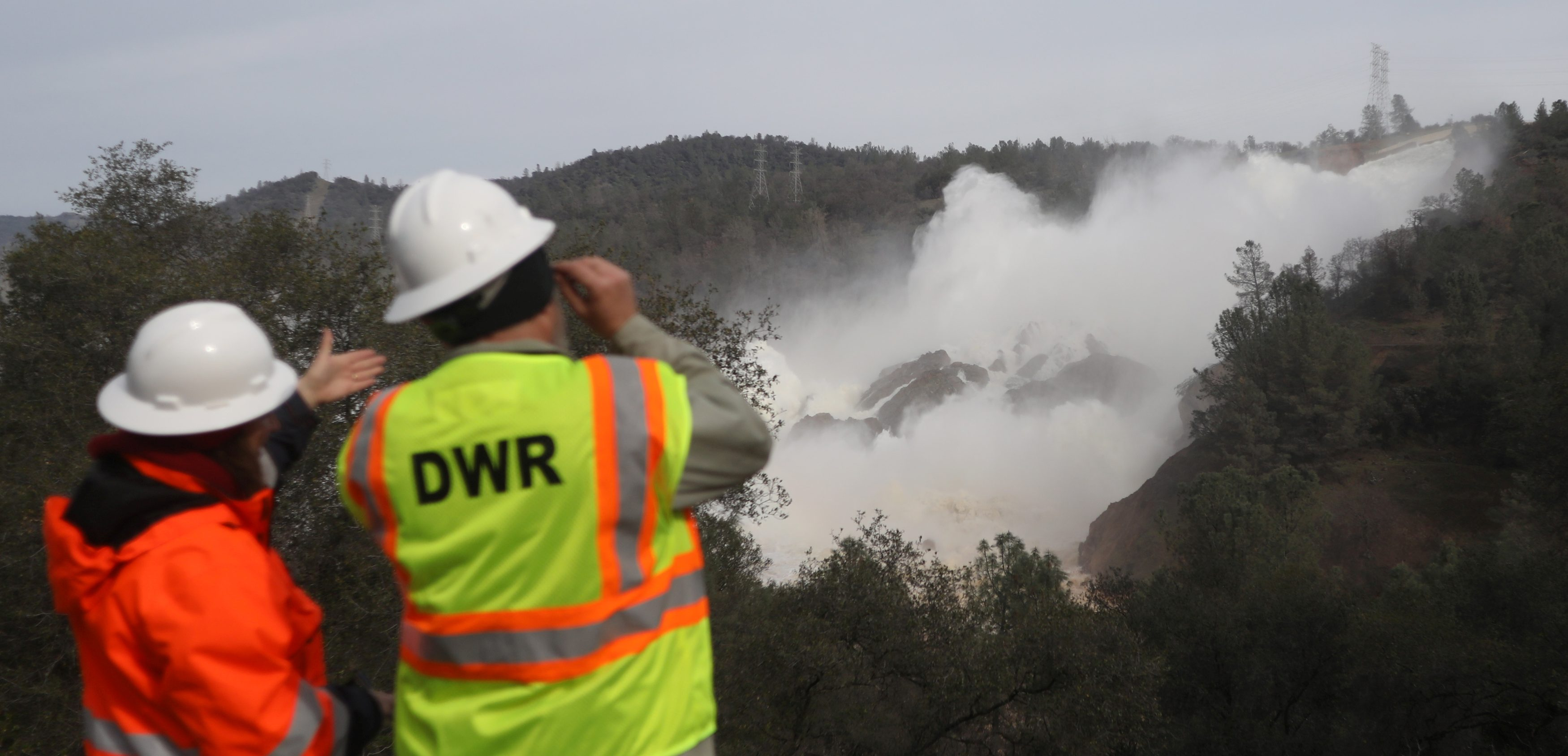 Staff with the California Department of Water Resources watch as water is released from the Lake Oroville Dam.