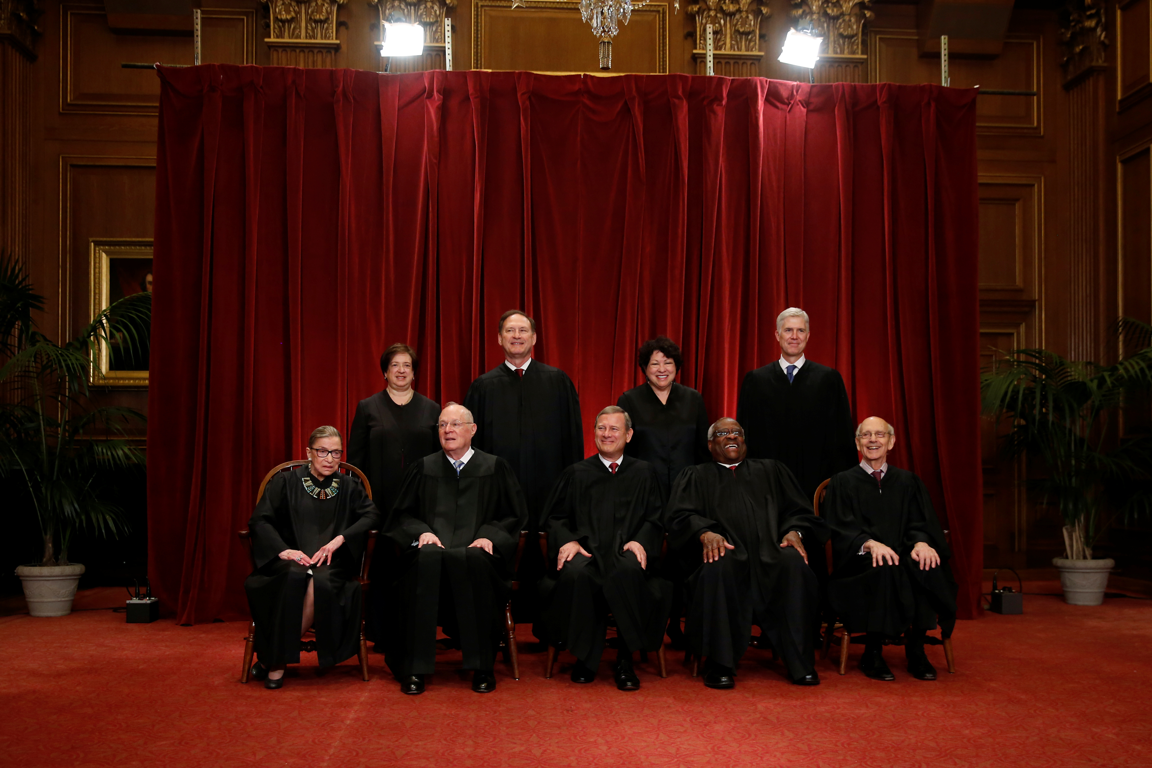 U.S. Chief Justice John Roberts (seated C) leads Justice Ruth Bader Ginsburg (front row, L-R), Justice Anthony Kennedy, Justice Clarence Thomas, Justice Stephen Breyer, Justice Elena Kagan (back row, L-R), Justice Samuel Alito, Justice Sonia Sotomayor, and Justice Neil Gorsuch in taking a new family photo including Gorsuch, their most recent addition, at the Supreme Court building in Washington, D.C, U.S., June 1, 2017. REUTERS/Jonathan Ernst - RC1263640740