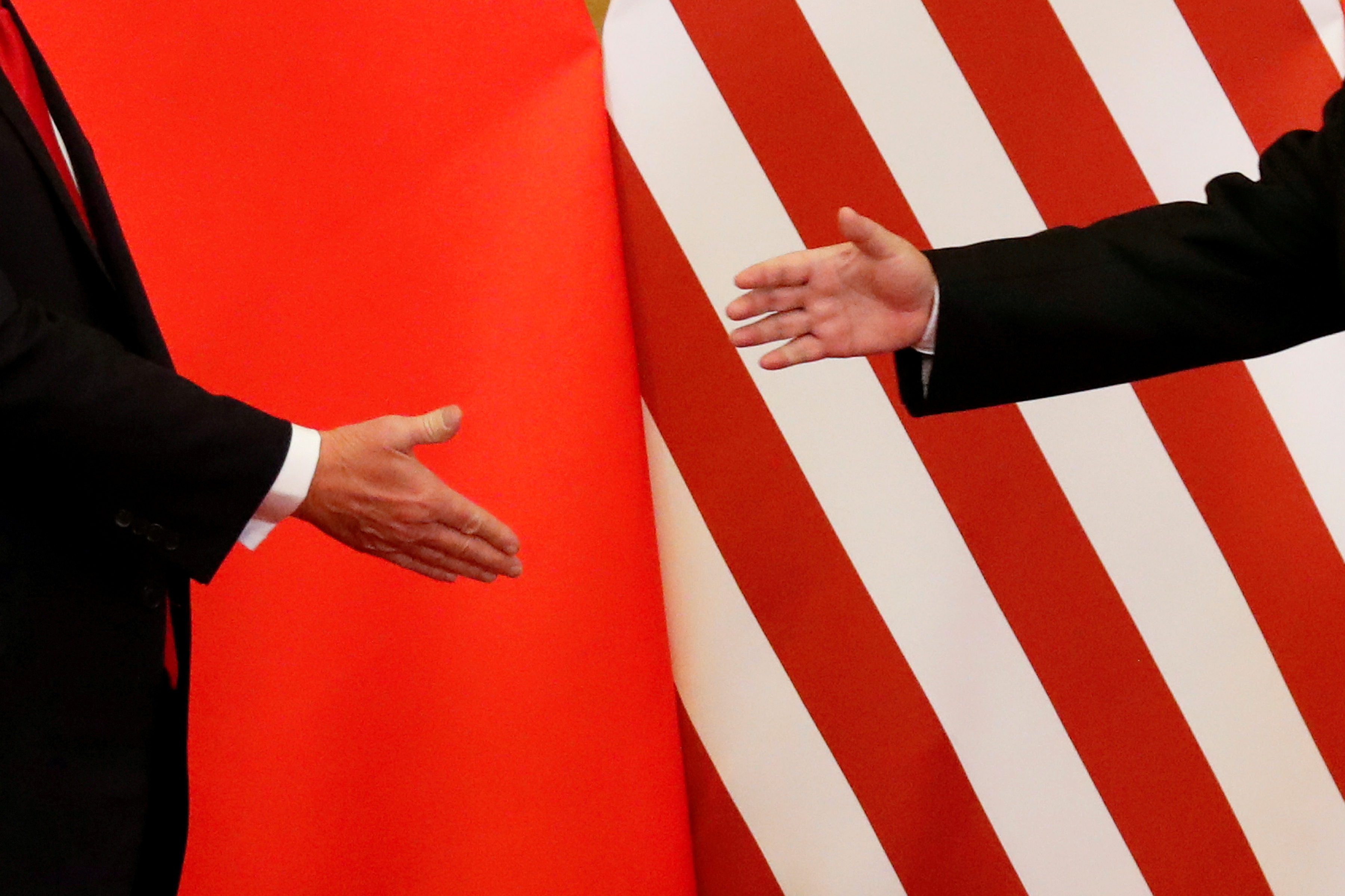 """U.S. President Donald Trump and China's President Xi Jinping shake hands after making joint statements at the Great Hall of the People in Beijing, China, November 9, 2017. Damir Sagolj: """"It's one of those """"how to make a better or at least different shot when two presidents shake hands several times a day, several days in row"""". If I'm not mistaken in calculation, presidents Xi Jinping of China and Donald Trump of the U.S. shook their hands at least six times in events I covered during Trump's recent visit to China. I would imagine there were some more handshakes I haven't seen but other photographers did. And they all look similar - two big men, smiling and heartily greeting each other until everyone gets their shot. But then there is always something that can make it special - in this case the background made of U.S. and Chinese flags. They shook hands twice in front of it, and the first time it didn't work for me. The second time I positioned myself lower and centrally, and used the longest lens I have to capture only hands reaching for a handshake."""" REUTERS/Damir Sagolj/File Photo  SEARCH """"POY TRUMP"""" FOR THIS STORY. SEARCH """"REUTERS POY"""" FOR ALL BEST OF 2017 PACKAGES.    TPX IMAGES OF THE DAY - RC1B1E5EF340"""