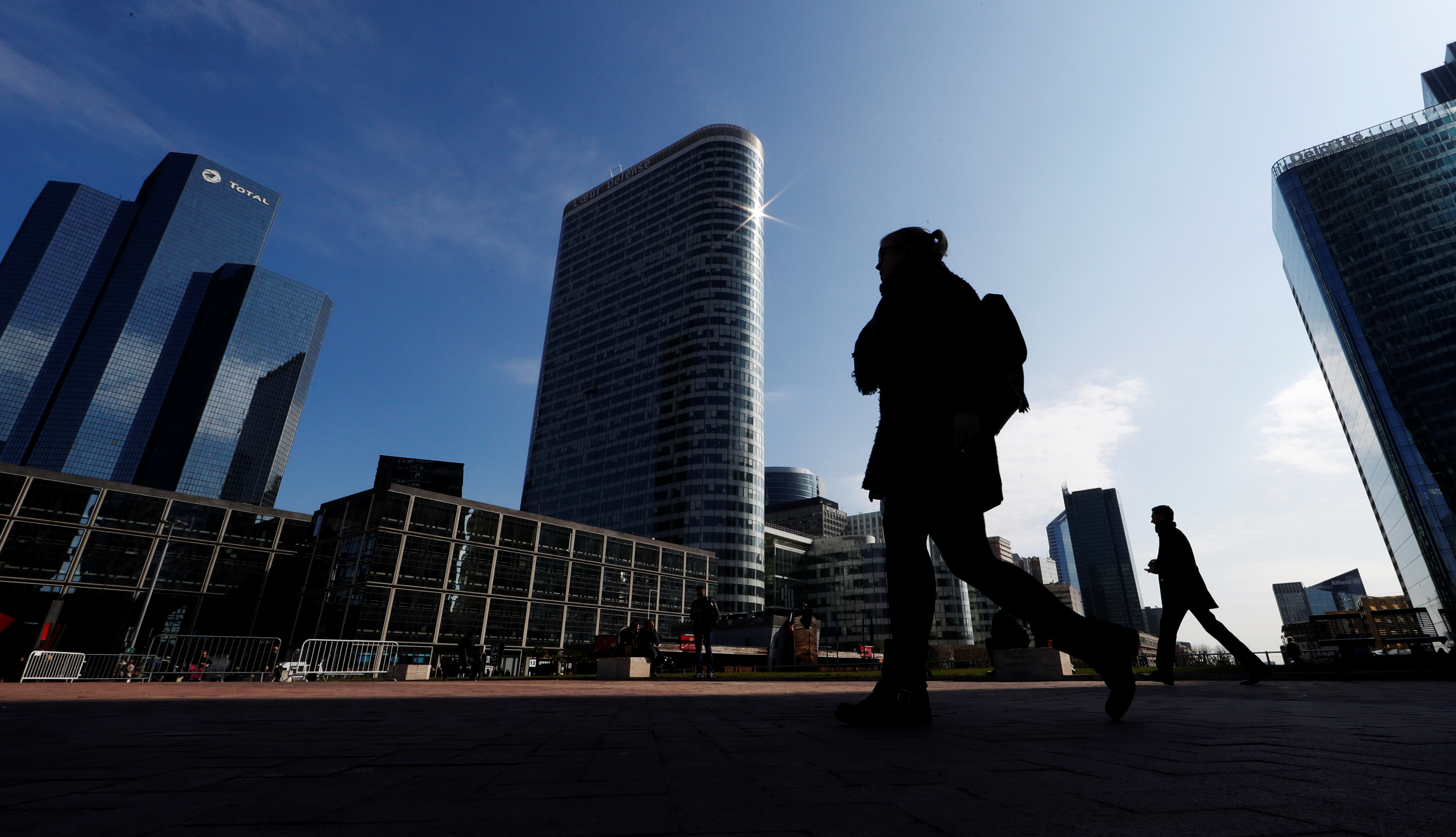 People walk on the esplanade of La Defense in the financial and business district of La Defense, west of Paris, France March 26, 2018. REUTERS/Gonzalo Fuentes - RC1D39CFF000