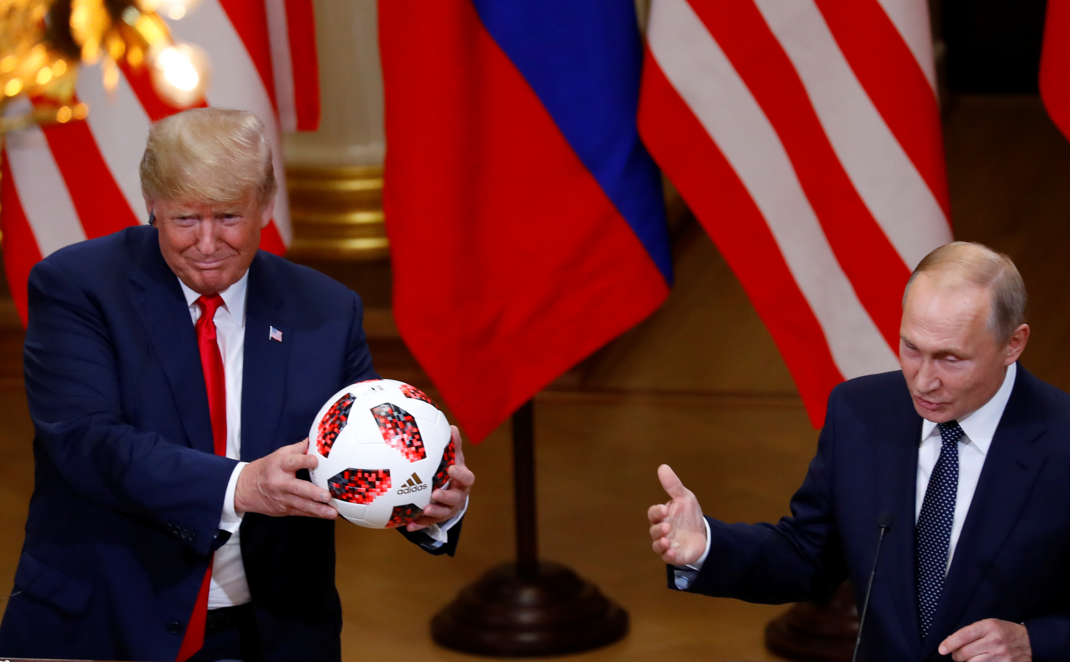 U.S. President Donald Trump receives a football from Russian President Vladimir Putin as they hold a joint news conference after their meeting in Helsinki, Finland, July 16, 2018. REUTERS/Leonhard Foeger - RC1EE9519B10