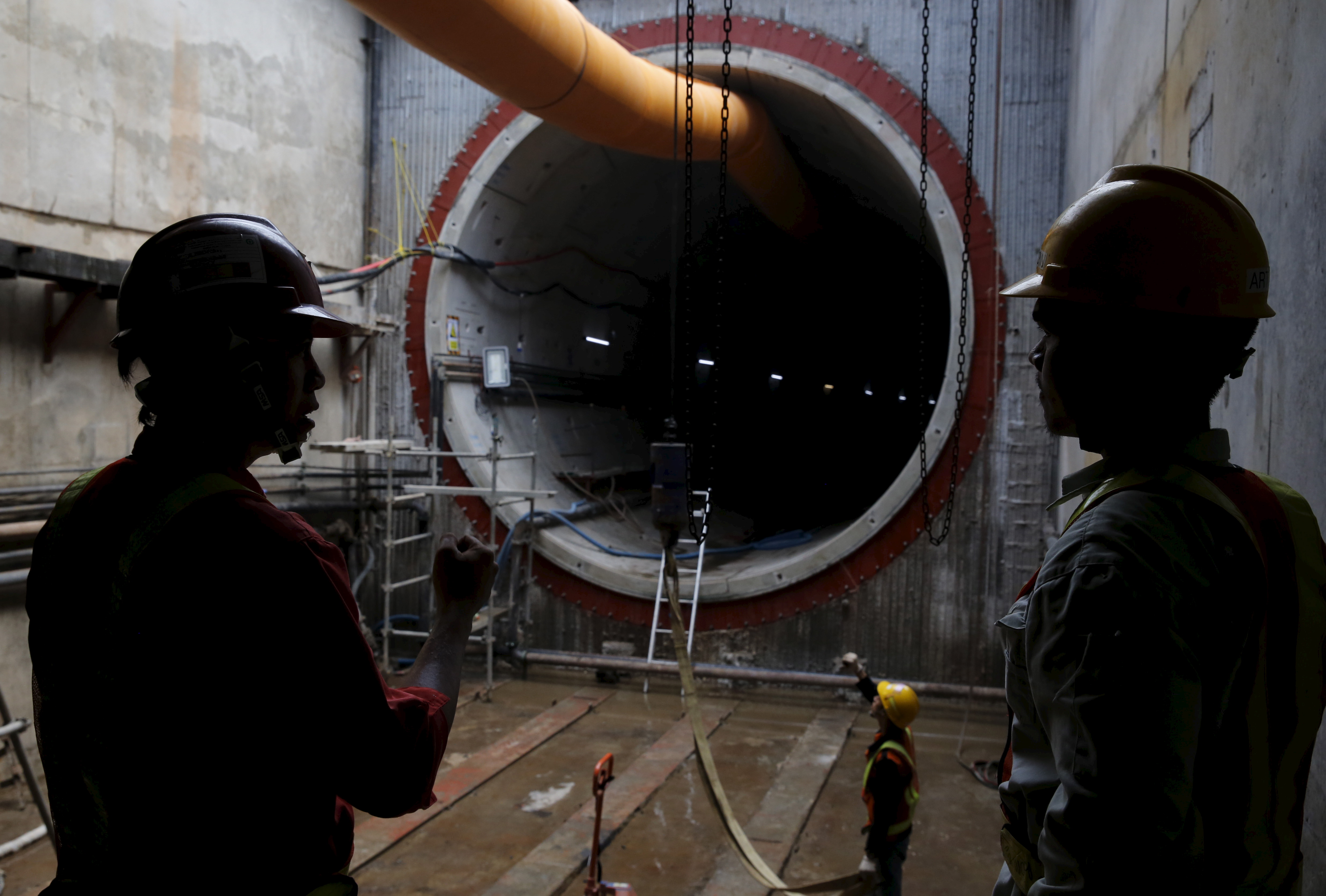 Construction workers stand near an underground MRT (Mass rapid transit system) tunnel in Jakarta
