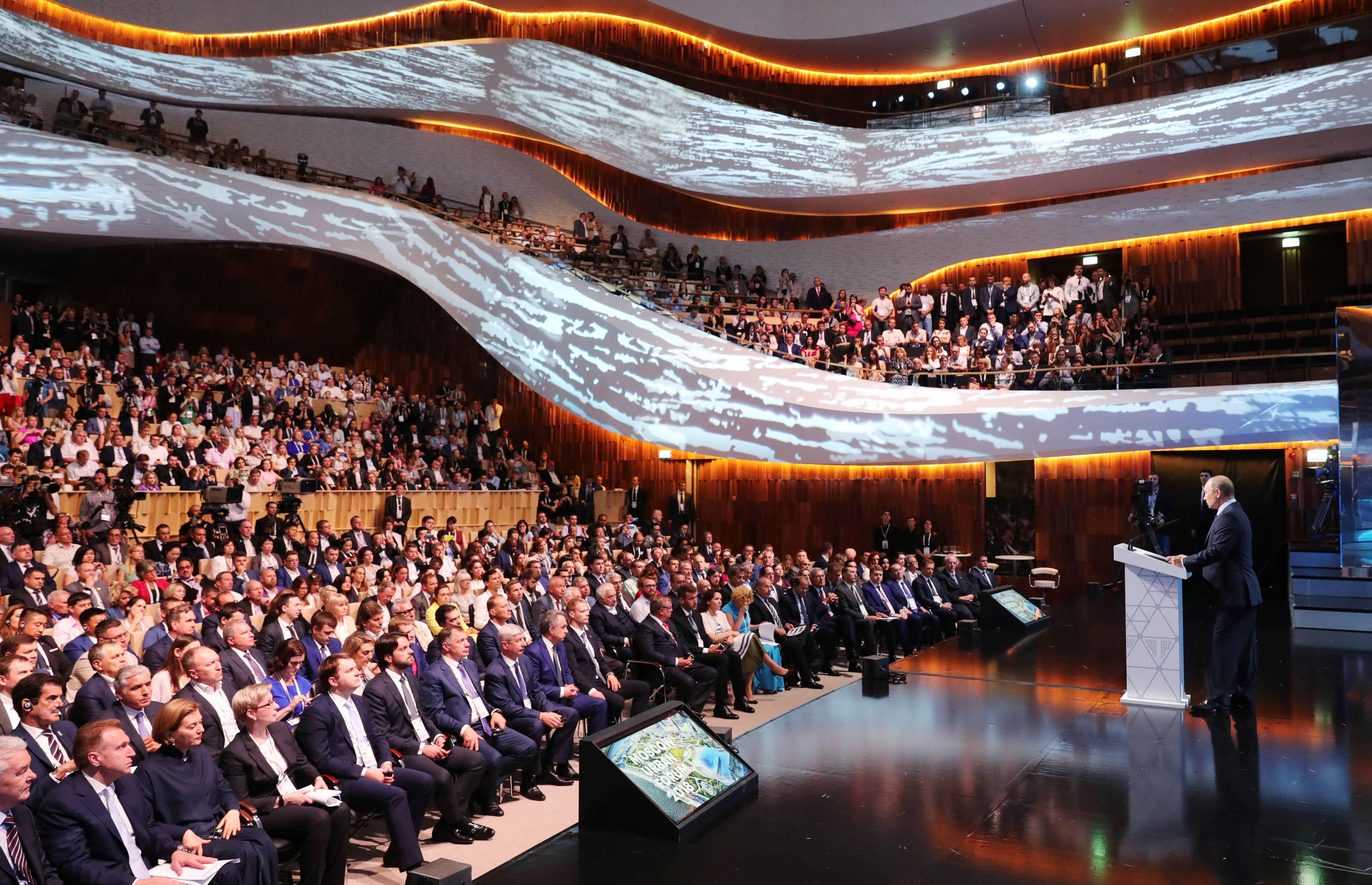 Participants listen to Russia's President Vladimir Putin during a session of Moscow Urban Forum 2018 at the Concert Hall of Zaryadye Park in Moscow, Russia July 18, 2018. Sputnik/Mikhail Klimentyev/Kremlin via REUTERS  ATTENTION EDITORS - THIS IMAGE WAS PROVIDED BY A THIRD PARTY. - RC142E176000