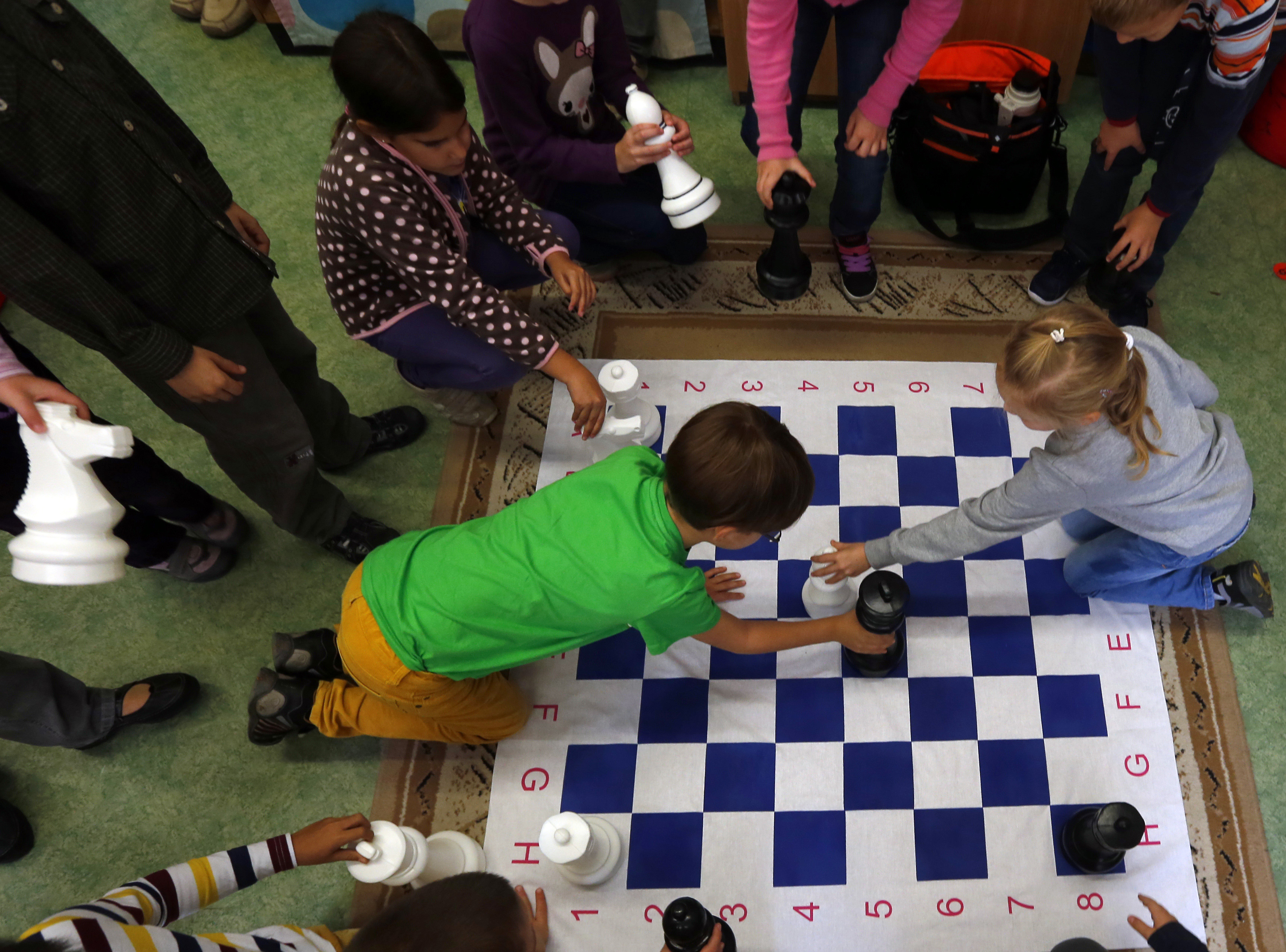 Children play chess at a classroom in the Dezso Lemhenyi school, which uses the new Chess Palace teaching programme of the world's best female chess player Judit Polgar, in Budapest October 15, 2013. With names like Jumpy Horse, Boom Rook and Tiny Pawn, pieces in the Chess Palace come to life and are like close friends who guide the children through difficult school subjects. They range in size from 1 cm (under half an inch) tall to a meter (three feet) in height. Chairs, walls and carpets also sport chess motifs. The pieces, whose combinations and moves represent mathematical, linguistic or musical patterns, help children develop their skills in chess and in their school studies while making the learning process a more joyous exercise. Picture taken October 15, 2013.REUTERS/Laszlo Balogh (HUNGARY - Tags: SPORT CHESS EDUCATION SOCIETY) - GM1E9AO1NK501