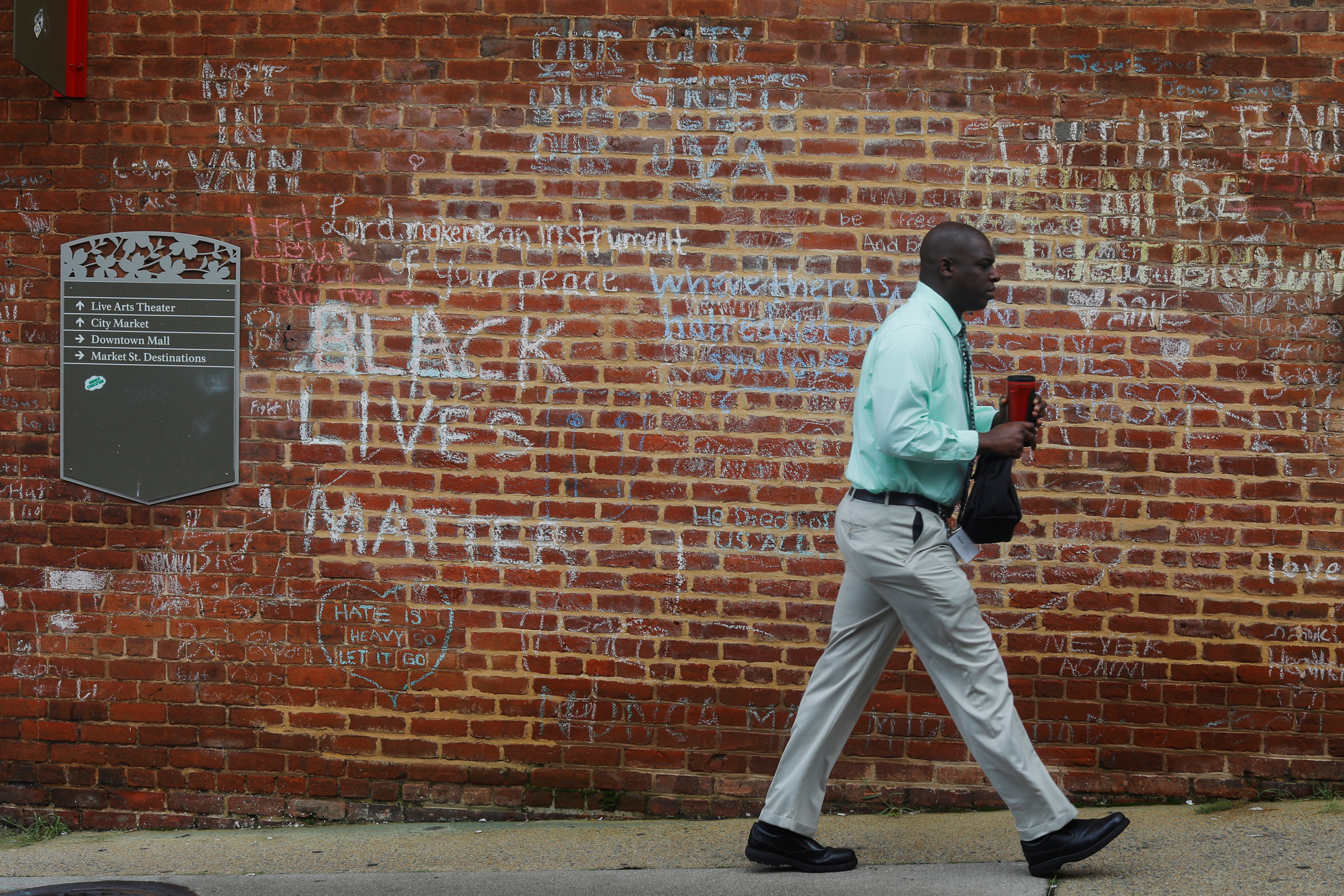 A man walks past tributes written at the site where Heather Heyer was killed during the 2017 white-nationalist rally in Charlottesville, Virginia, U.S., August 1, 2018.  Picture taken August 1, 2018. REUTERS/Brian Snyder - RC19E176BEC0