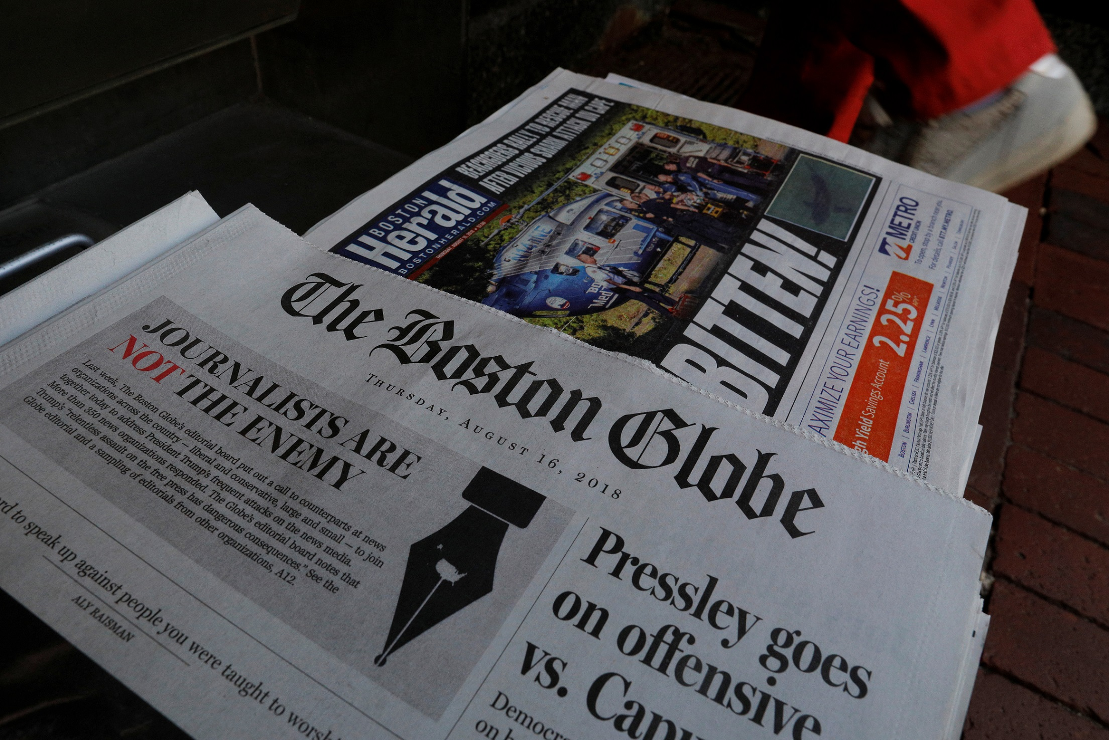 A customer walks past the front page of the Boston Globe newspaper referencing their editorial defense of press freedom and a rebuke of President Donald Trump for denouncing some media organizations as enemies of the American people, part of a nationwide editorial effort coordinated by the Boston Globe, at a newsstand in Cambridge, Massachusetts, U.S., August 16, 2018.     REUTERS/Brian Snyder - RC13AB4553F0