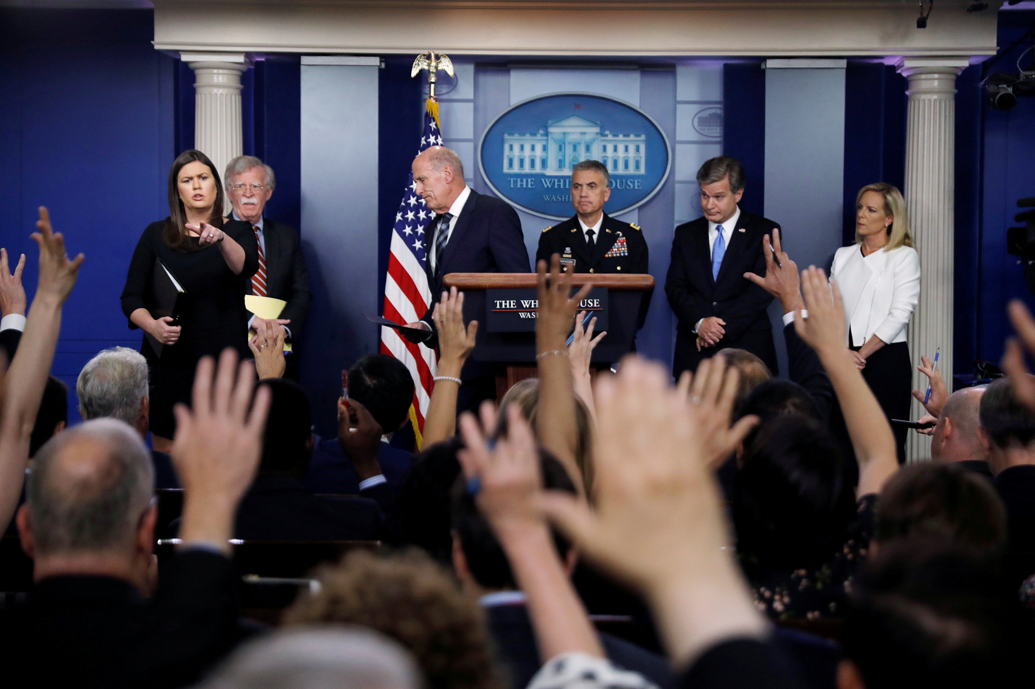 White House Press Secretary Sarah Huckabee Sanders points to questioners as National Security Advisor John Bolton, U.S. Director of National Intelligence Dan Coats, National Security Agency (NSA) Director General Paul Nakasone, FBI Director Christopher Wray and Department of Homeland Security (DHS) Secretary Kirstjen Nielsen hold a briefing on election security in the White House press briefing room at the White House in Washington, U.S., August 2, 2018.  REUTERS/Carlos Barria      TPX IMAGES OF THE DAY - RC1CC3F64980
