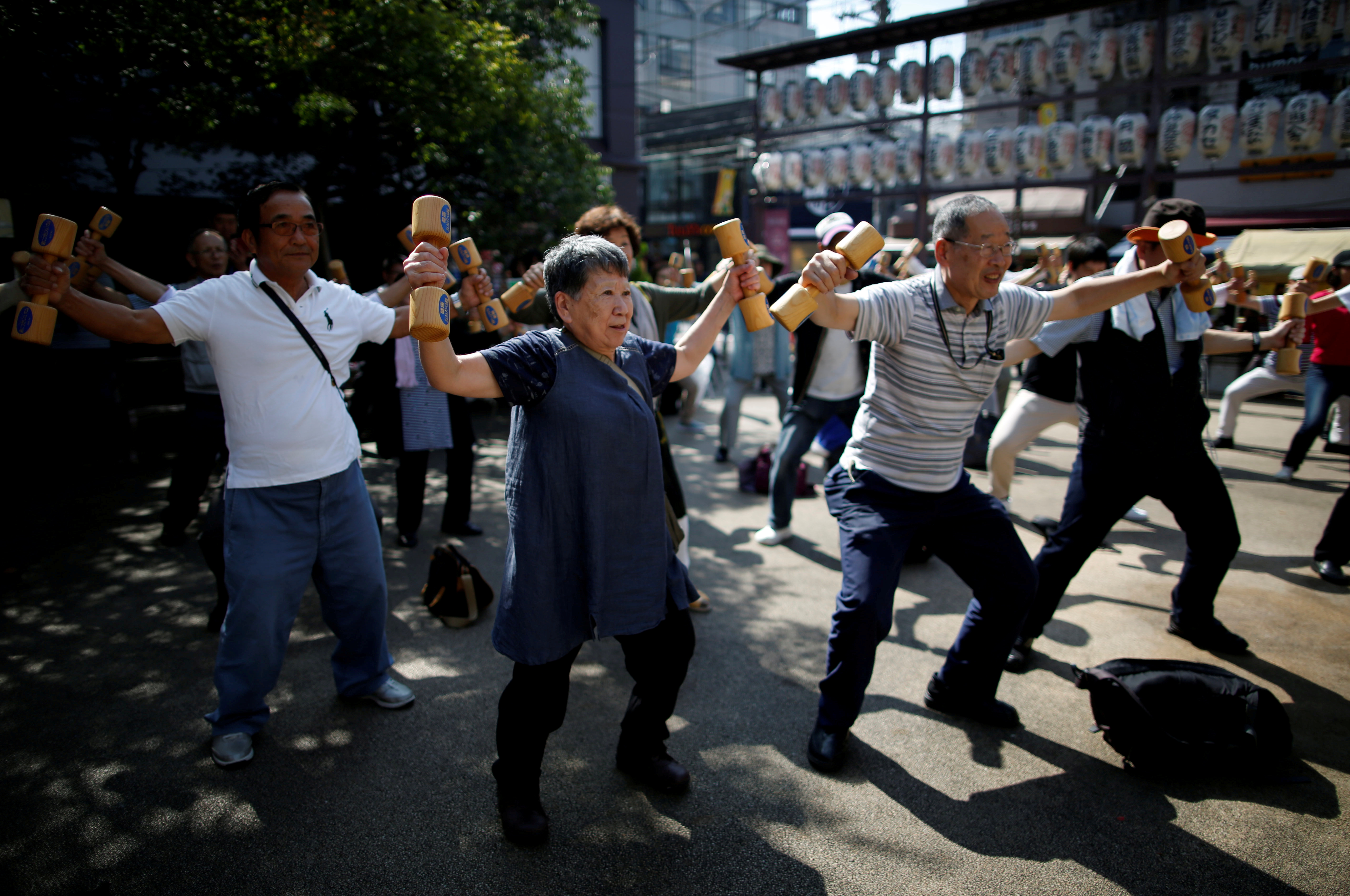 """Participants including elderly and middle-aged people exercise with wooden dumbbells during a health promotion event to mark Japan's """"Respect for the Aged Day"""" at a temple in Tokyo's Sugamo district, an area popular among the Japanese elderly, September 17, 2018. REUTERS/Issei Kato      TPX IMAGES OF THE DAY - RC14EDF2A330"""
