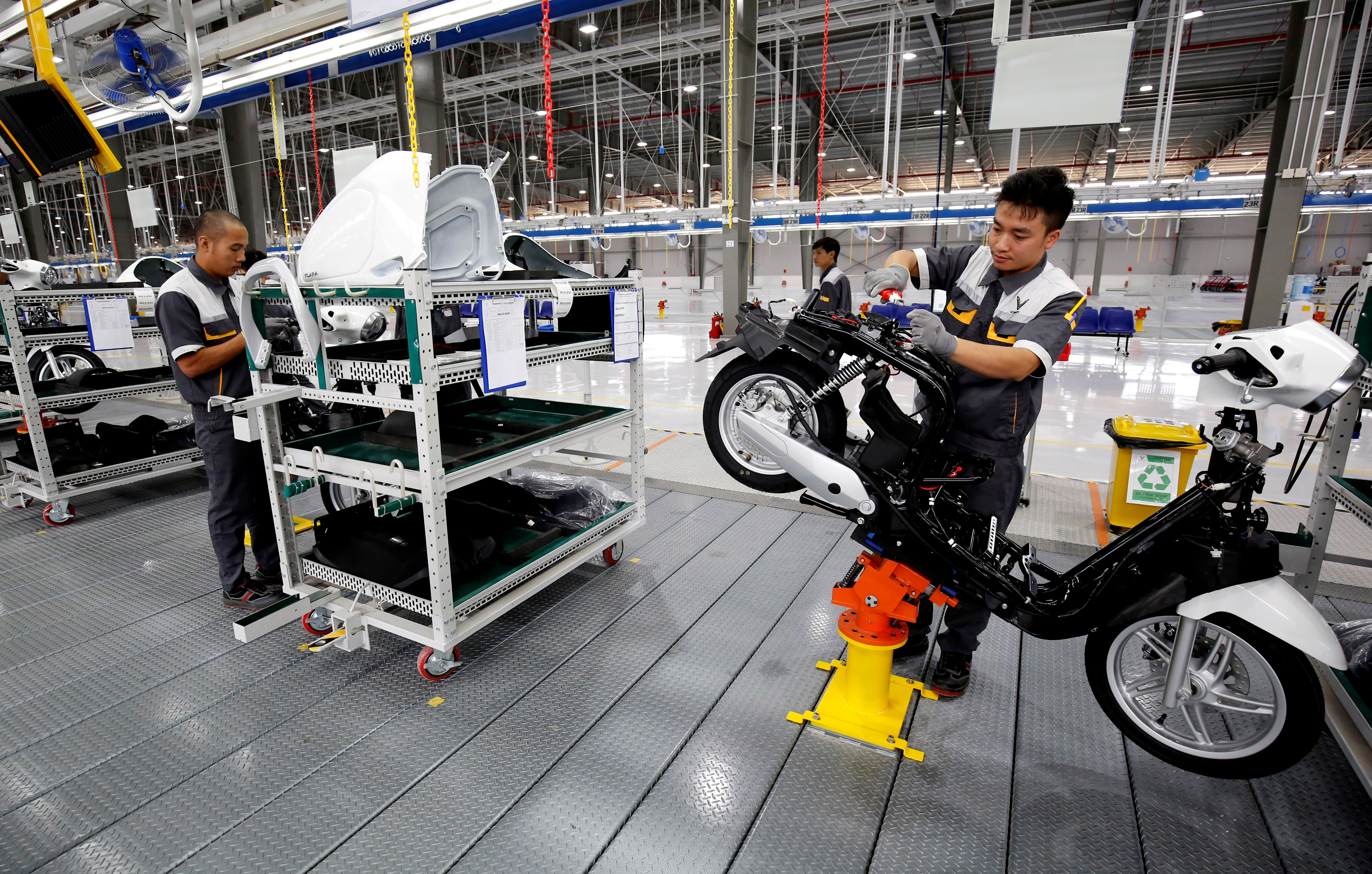 Men work at an e-scooter assembly line of Vinfast Auto and Motorcycle factory in Hai Phong city, Vietnam November 3, 2018. REUTERS/Kham - RC1468580640
