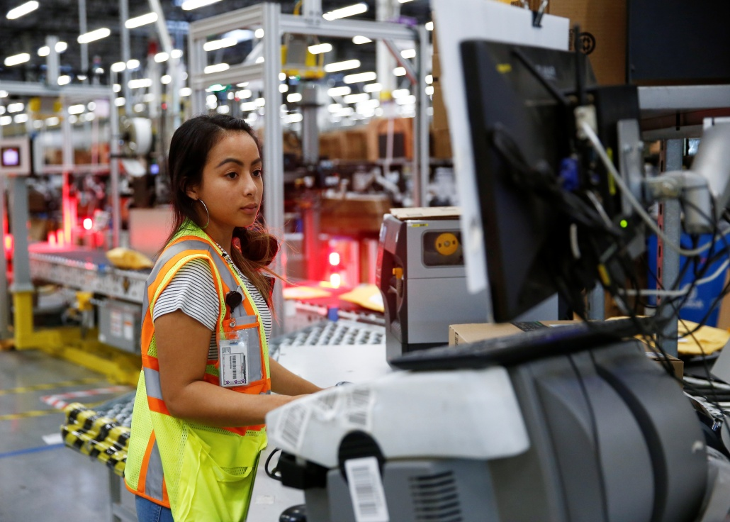 Employee Stanaleen Greenman works on processing packages kicked out by the automated scanning and labeling system at the Amazon fulfillment center in Kent, Washington, U.S., October 24, 2018. REUTERS/Lindsey Wasson - RC1C49A3AD10