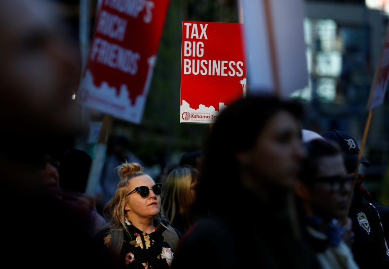 A woman holds a sign supporting the taxation of big businesses during a protest in front of the Amazon Spheres to demand that the city of Seattle tax the largest corporations to help fund affordable housing, according to organizers, in Seattle, Washington, U.S., April 10, 2018.  REUTERS/Lindsey Wasson - RC1F0EDB1690
