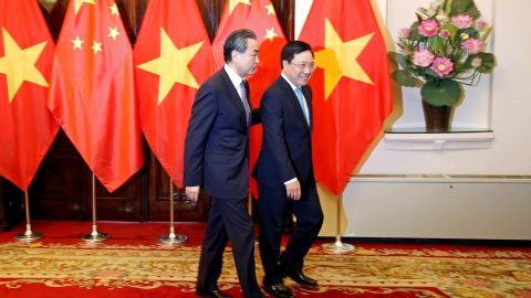 China's State Councilor and Foreign Minister Wang Yi (L) and Vietnam's Deputy Prime Minister and Foreign Minister Pham Binh Minh walk to a meeting room at the Government Guesthouse in Hanoi, Vietnam April 1, 2018. REUTERS/Kham - RC142FA2A510