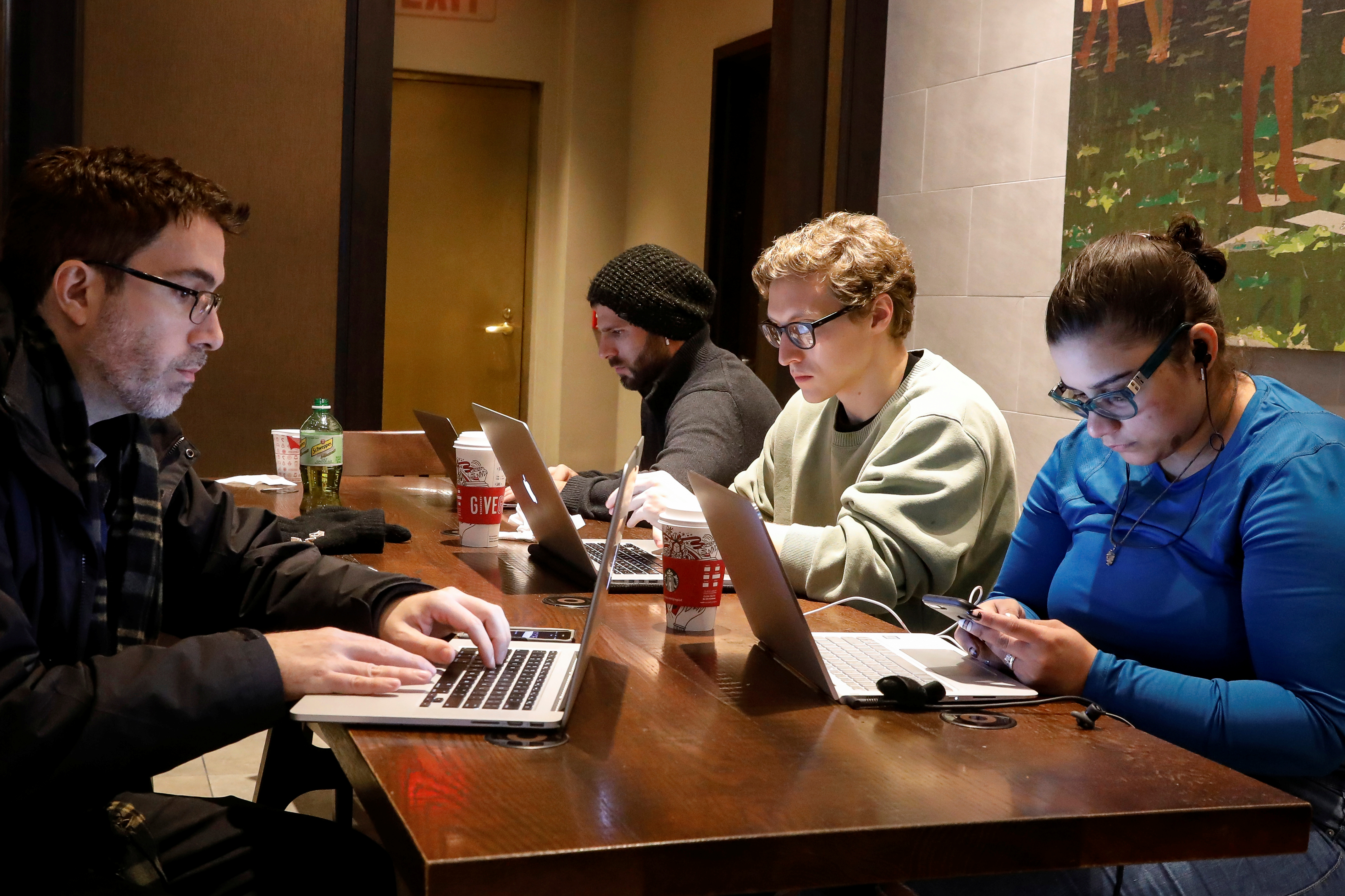 Customers use the internet at a Starbucks in the financial district in New York City, U.S., December 14, 2017. REUTERS/Brendan McDermid - RC174920FF60