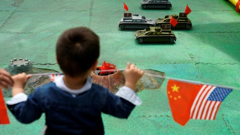 A boy looks at remote control tank toys next to the flags of China and the U.S. at a park in Shanghai, China, May 29, 2019. REUTERS/Aly Song - RC1502D3D7F0