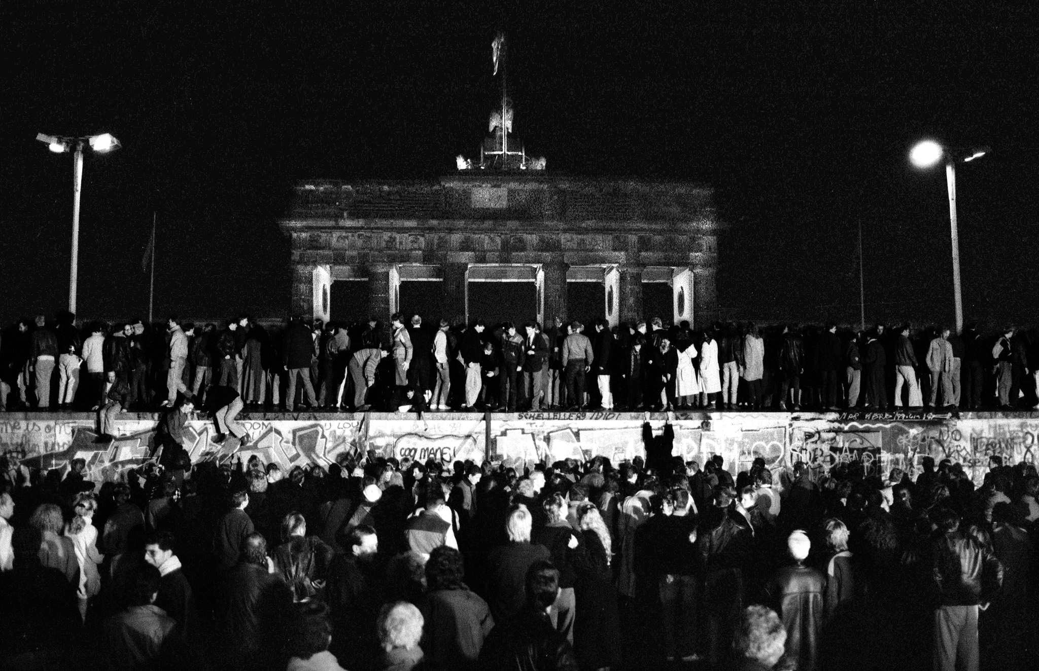 East and West Germans celebrate on the Berlin Wall at the Brandenburg Gate after the opening of the border on November 9, 1989. (Reuters)