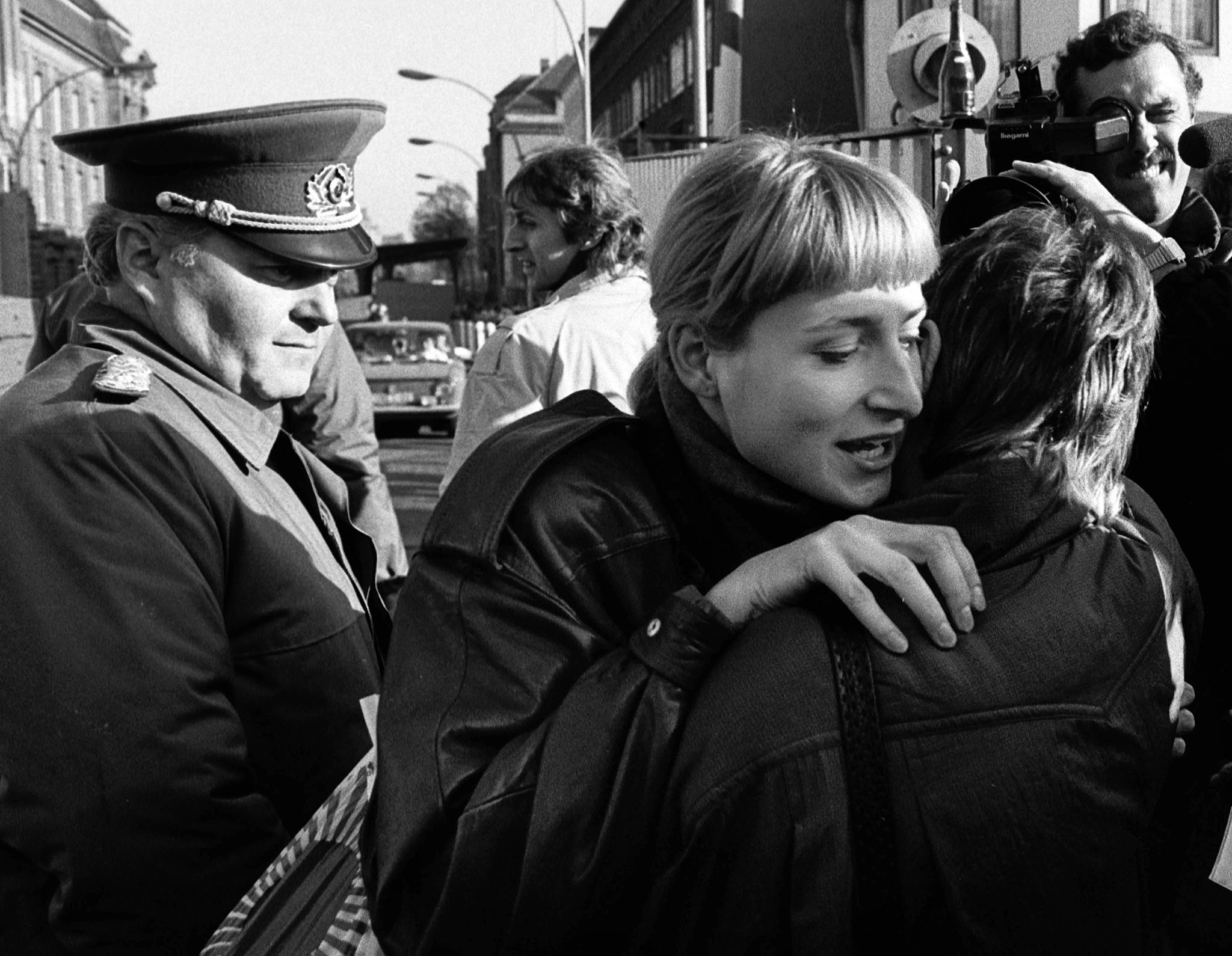 An East Berliner and a West Berliner embrace while a border soldier looks on, November 10, 1989. (Reuters)