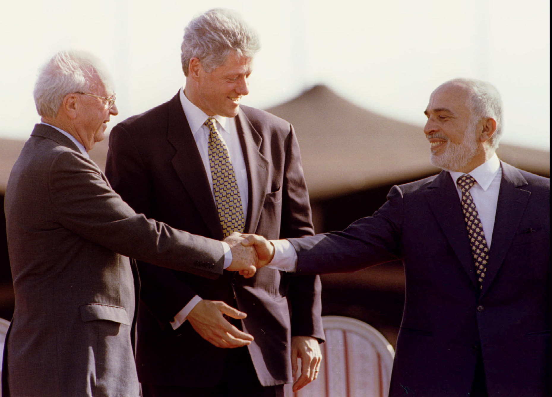 US President Bill Clinton applauds as Jordan s King Hussein reaches out and shakes hands with Israeli Prime Minister Yitzhak Rabin (L) at the end of the Israeli - Jordanian peace treaty signing ceremony - PBEAHUNIEEZ