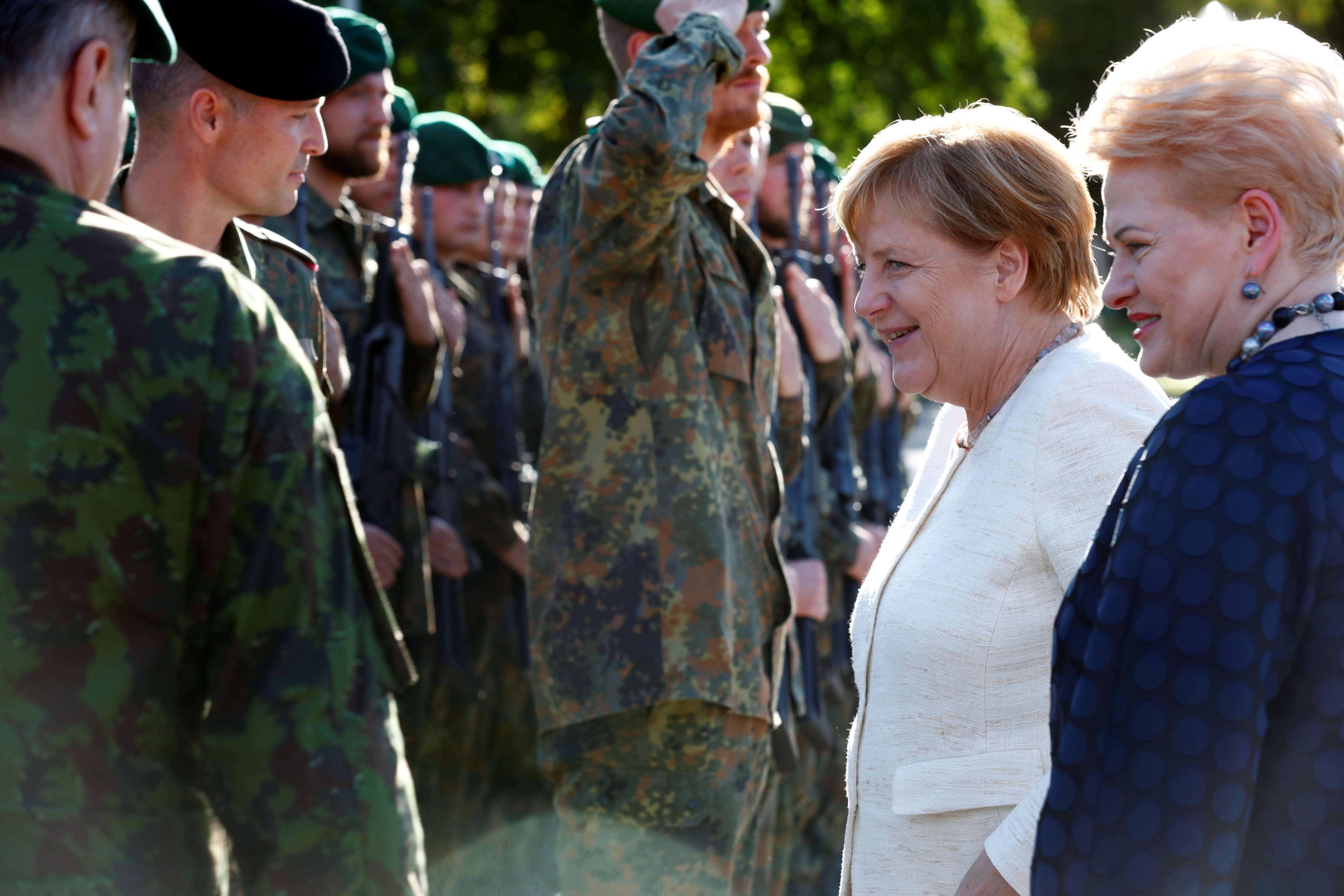 German Chancellor Angela Merkel and then-Lithuanian President Dalia Grybauskaitė visit German NATO troops deployed in Lithuania. (Ints Kalnins/Reuters)