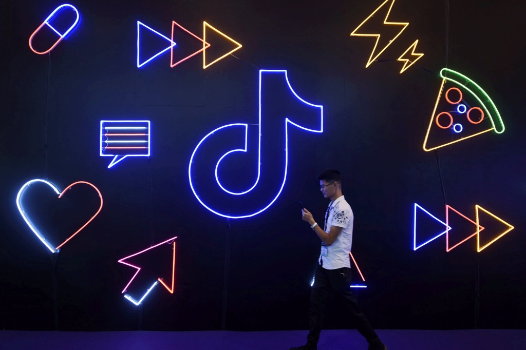A man holding a phone walks past a sign of Chinese company ByteDance's app TikTok, known locally as Douyin, at the International Artificial Products Expo in Hangzhou, Zhejiang province, China October 18, 2019. Picture taken October 18, 2019.  REUTERS/Stringer  ATTENTION EDITORS - THIS IMAGE WAS PROVIDED BY A THIRD PARTY. CHINA OUT. - RC171198B320