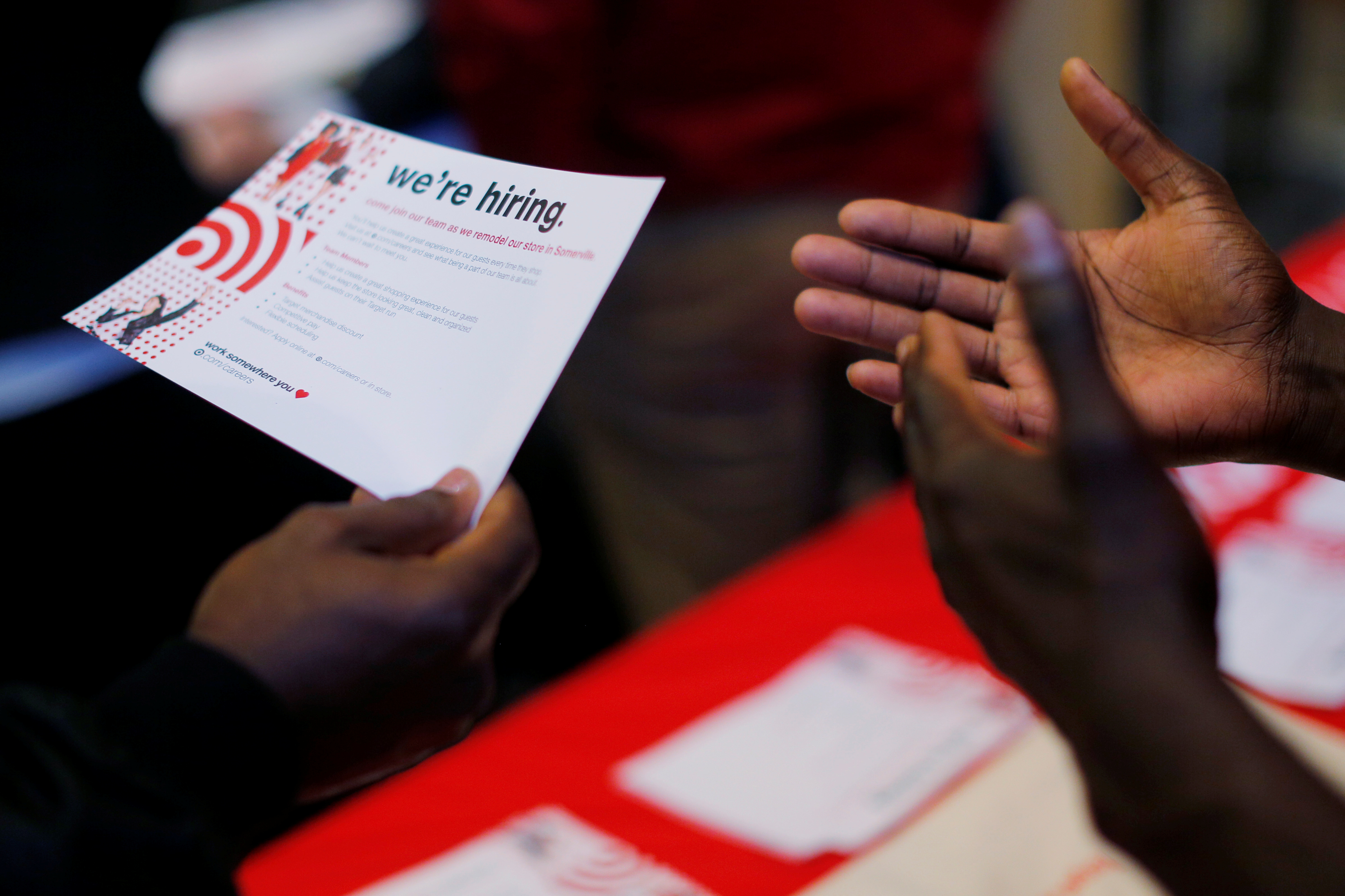 """A job seeker holds a """"We're Hiring"""" card while talking to a representative from Target at a City of Boston Neighborhood Career Fair on May Day in Boston, Massachusetts, U.S., May 1, 2017.   REUTERS/Brian Snyder - RC1B6FFBEDC0"""