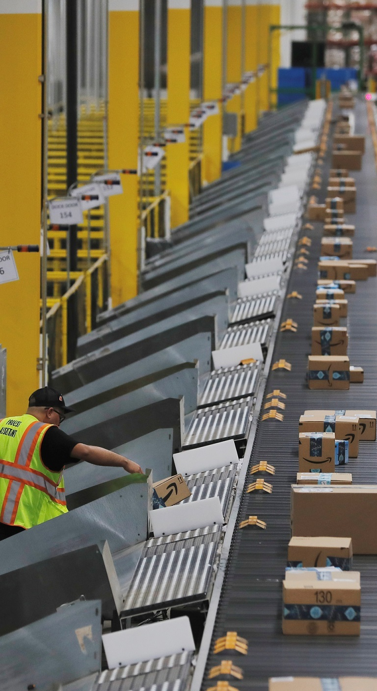 Amazon packages are pushed onto ramps leading to delivery trucks by a robotic system as they travel on conveyor belts inside of an Amazon fulfillment center on Cyber Monday in Robbinsville, New Jersey, U.S., December 2, 2019. REUTERS/Lucas Jackson
